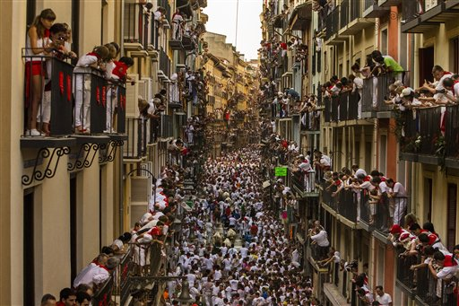 People watch as Jandilla fighting bulls and revelers run during the running of the bulls at the San Fermin festival in Pamplona, Spain, Tuesday.