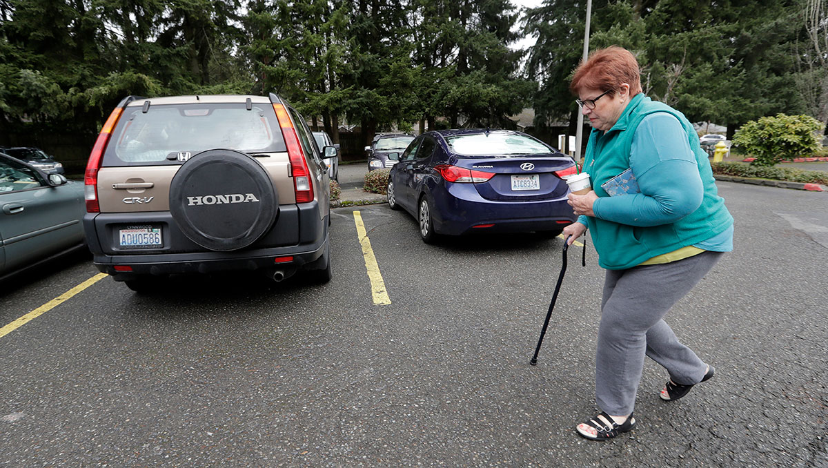 In this Monday, March 5, 2018, photo, Paula Lowery, 70, walks to her Honda CR-V where she lives with her two cats in the church parking lot she shares with two-dozen or so other vehicles and their occupants, homeless single women, in Kirkland, Wash. Some of the obstacles faced by the women in finding permanent housing may soon become illegal in Washington state, where legislators are advancing a bill that would prohibit landlords from turning away tenants who rely on Section 8 vouchers, Social Security or veterans benefits. (AP Photo/Elaine Thompson)