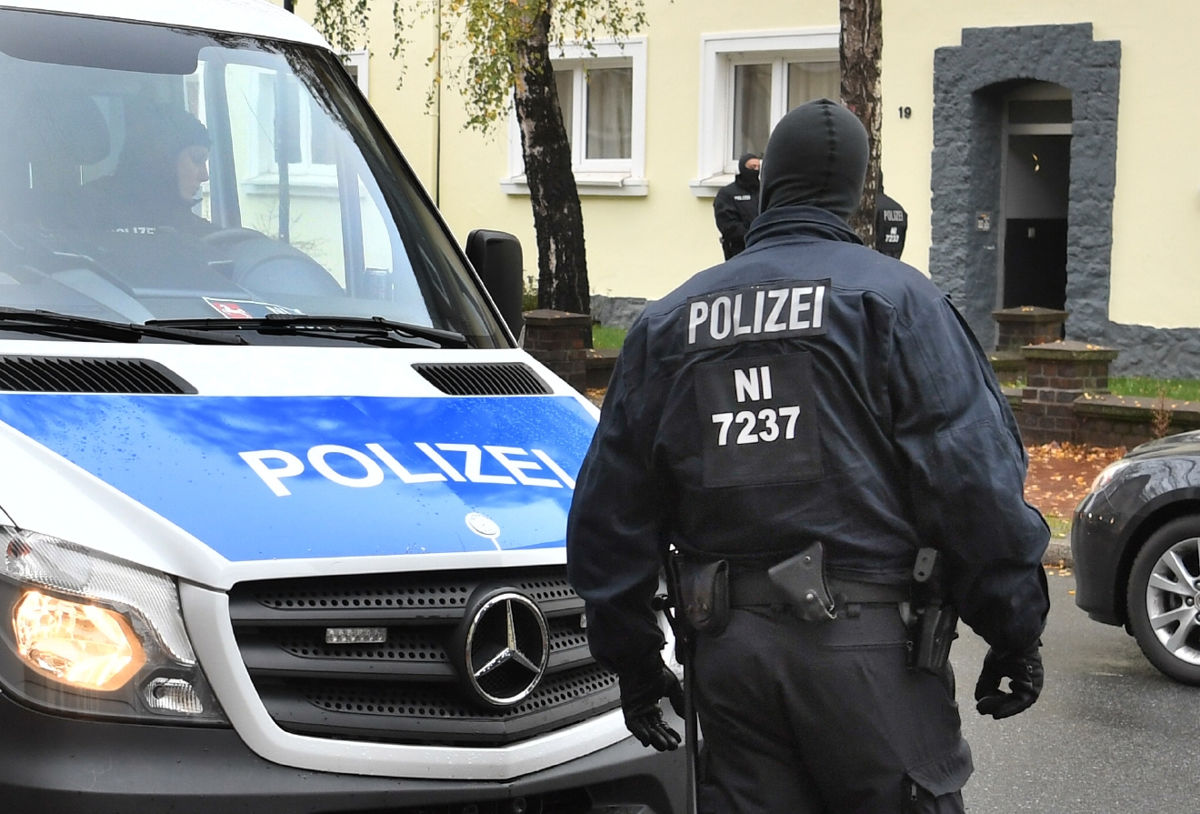 Police officers seach a residential building opposite the German-Speaking Islamic Circle Hildesheim mosque in Hildesheim, Germany, Tuesday, Nov. 8, 2016. German security authorities arrested five men Tuesday on allegations they aided the Islamic State group in Germany, recruiting members and providing financial and logistical help. (Julian?Stratenschulte/dpa via AP)