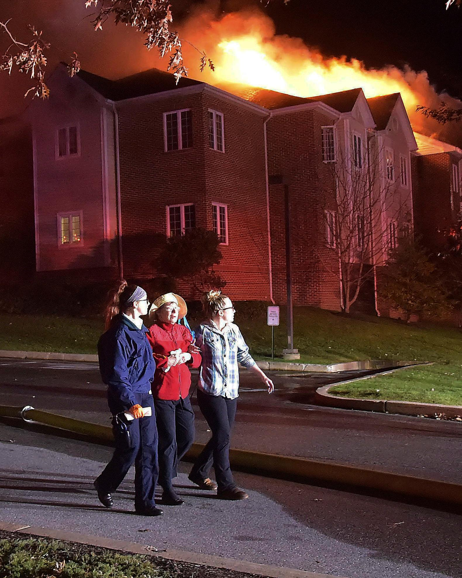 A resident of the Barclay Friends Senior Living Community is assisted away from the scene of a fire as the senior care facility burned late Thursday night, Nov. 16, 2017, in West Chester, Pa. The fire quickly spread to multiple buildings, forcing residents to evacuate outside into the cold. Chester County emergency officials say at least 20 people have been taken to area hospitals for treatment. (Pete Bannan/Daily Local News via AP)