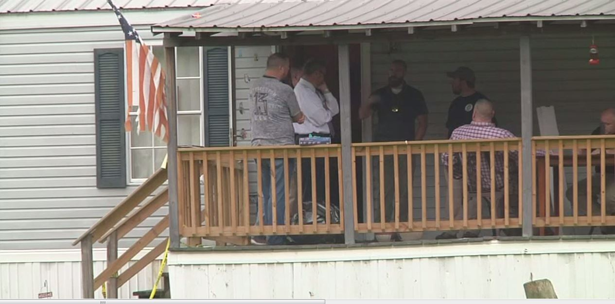 Law enforcement officers gather as they investigate a quadruple homicide in Lawrence County, Ohio, that claimed the lives of three adults and a 7-year-old boy. (WCHS/WVAH)