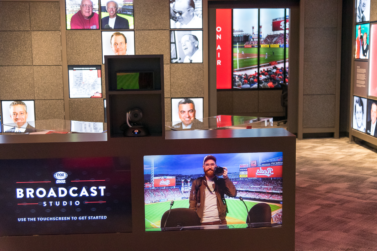 An interactive feature inside the broadcasters' exhibit lets you sit at the desk and pretend you're on TV. / Image: Phil Armstrong, Cincinnati Refined // Published: 4.20.19