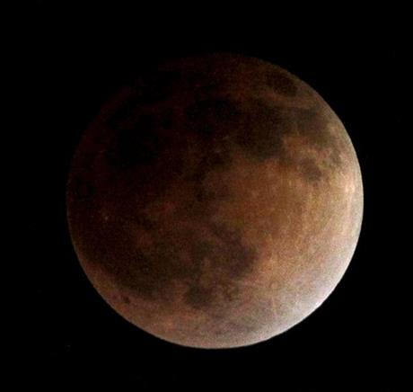 As the moon completely crosses the earth's shadow, the first of four total lunar eclipses, called the Blood Moon, occur in Whittier, Ca., USA on Tuesday, April 15, 2014.