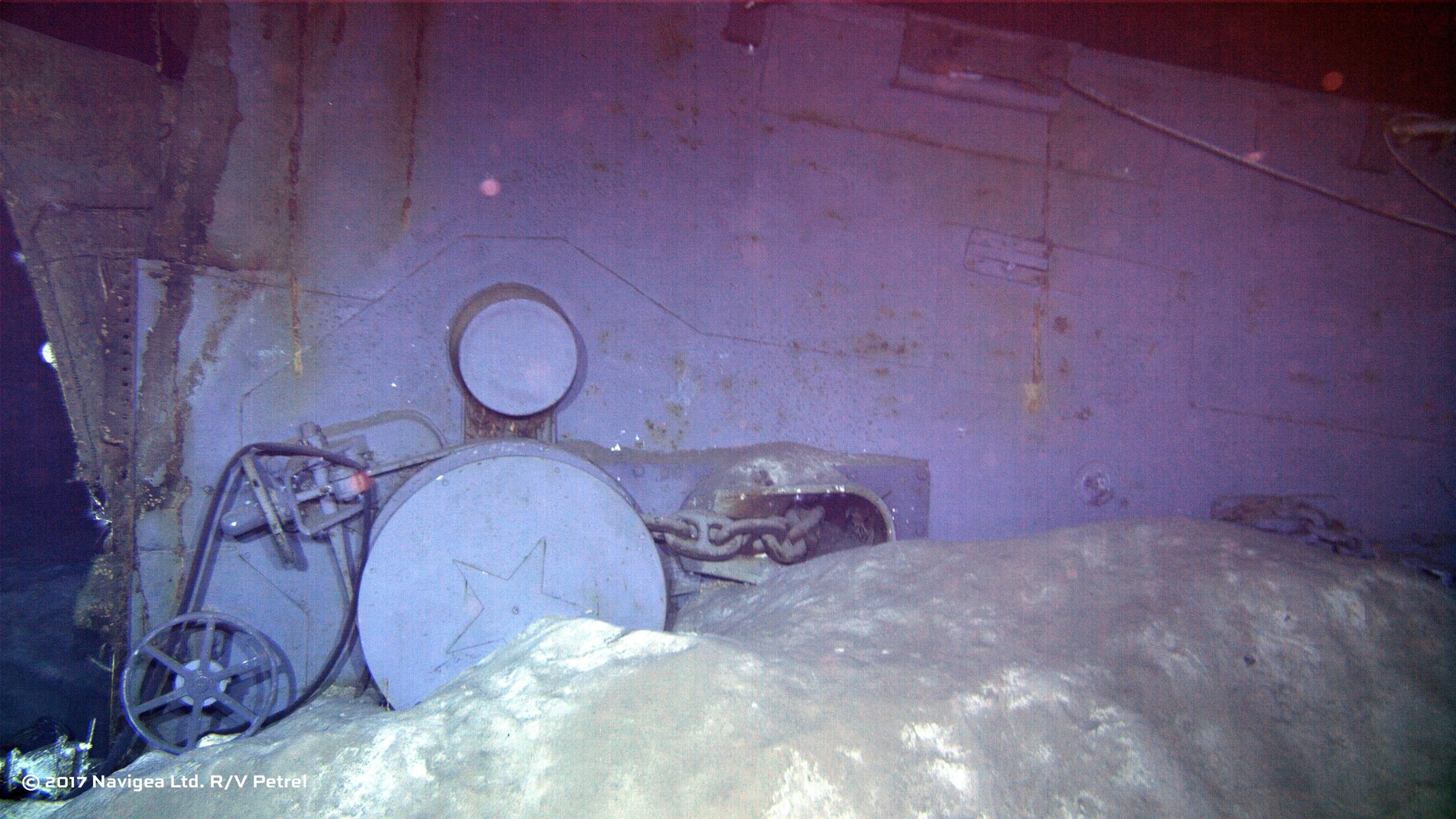 An image shot from a remotely operated vehicle shows wreckage which appears to be one of the two anchor windlass mechanisms from the forecastle of the ship.  Note the star-emblazoned capstans in this photo dated July 12, 1945 just weeks before the ship was lost.  Photo courtesy Paul G. Allen.