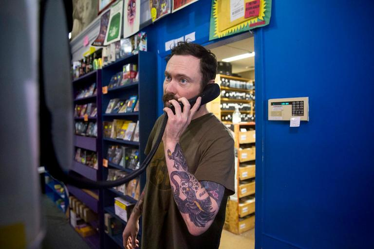 <p>Day Manager Jason Dodson answers the phone at Scarecrow Video, the film rental store that has been serving Seattle for 30 years. In 2014, the collection had grown to become such a significant archive that a non-profit was formed. The store continues to grow at a rate of 3,000-5,000 titles each year, representing 129 countries and over 126 languages. (Sy Bean / Seattle Refined)</p>
