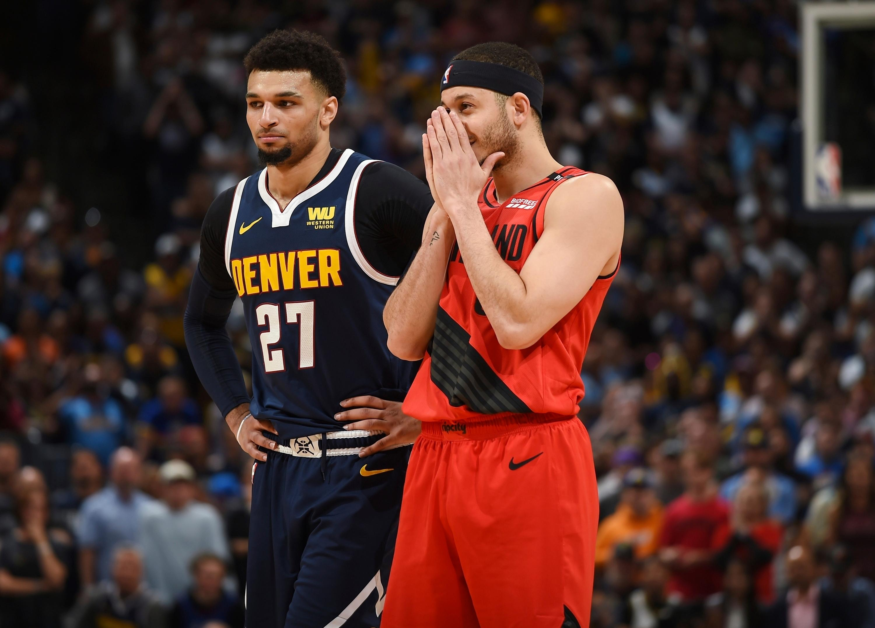 CORRECTS BYLINE IN SIGNOFF TO JOHN LEYBA NOT DAVID ZALUBOWSKI Denver Nuggets guard Jamal Murray, left, looks on as Portland Trail Blazers guard Seth Curry reacts as time runs down in the second half of Game 7 of an NBA basketball second-round playoff series Sunday, May 12, 2019, in Denver. The Trail Blazers won 100-96. (AP Photo/John Leyba)