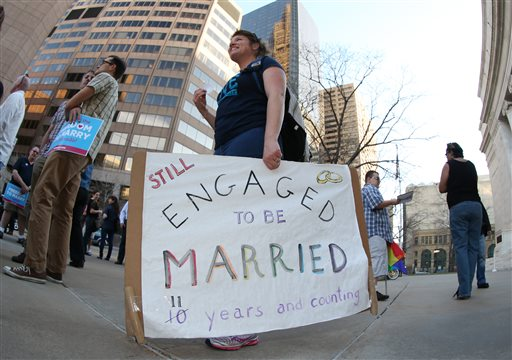 Anna Simon of Denver carries a sign about the state of her marriage to her partner at a protest outside the Federal Courthouse in downtown Denver.