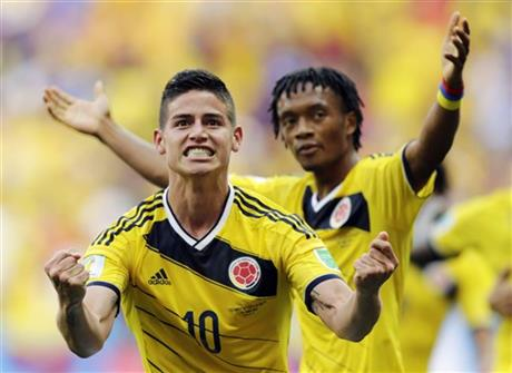 Colombia's James Rodriguez (10) celebrates with teammate Colombia's Juan Cuadrado after scoring his side's first goal during the group C World Cup soccer match between Colombia and Ivory Coast at the Estadio Nacional in Brazil, Thursday, June 19, 2014.