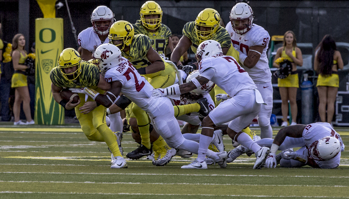 Oregon quarterback Braxton Burmeister (#11) pulls away from the Washington State defense. The Oregon Ducks trail the Washington State Cougars 10 to 13 at the end of the first half. Photo by Ben Lonergan, Oregon News Lab