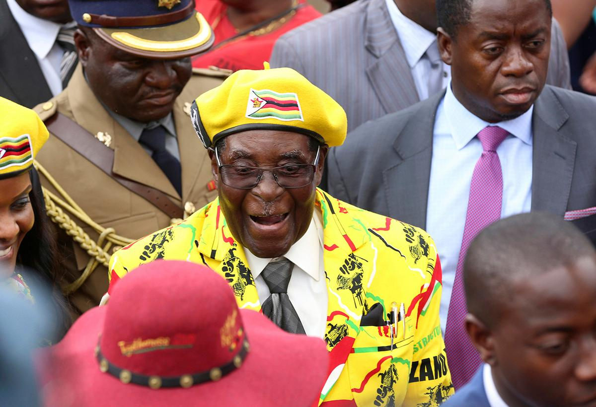 "FILE -- In this Wednesday, Nov. 8, 2017 file photo, Zimbabwean President Robert Mugabe, centre, arrives for a solidarity rally in Harare.  Armored personnel carriers were seen Tuesday Nov. 14, 2017, outside the capital a day after the army commander Chiwenga threatened to ""step in"" to calm political tensions over the president's firing of his deputy.(AP Photo/Tsvangirayi Mukwazhi, File)"