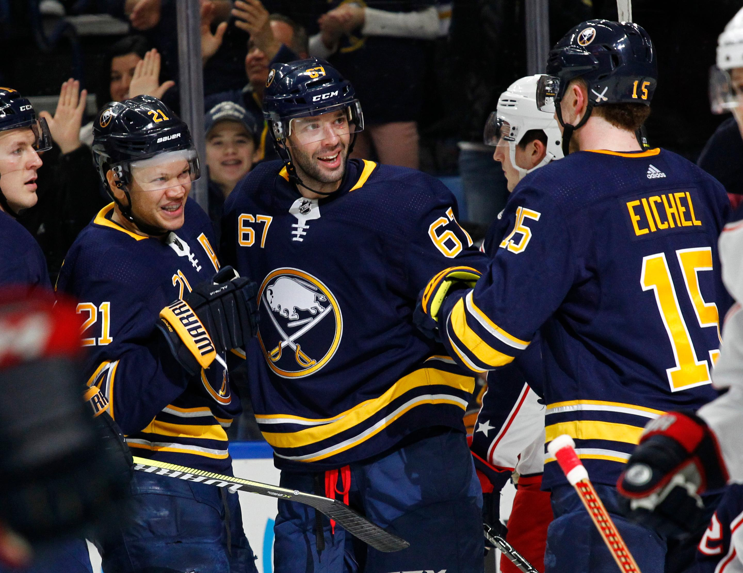 Buffalo Sabres' Kyle Okposo (21) and Benoit Pouliot (67) celebrate a goal during the first period of an NHL hockey game against the Columbus Blue Jackets on Thursday, Jan. 11, 2018, in Buffalo, N.Y. (AP Photo/Jeffrey T. Barnes)