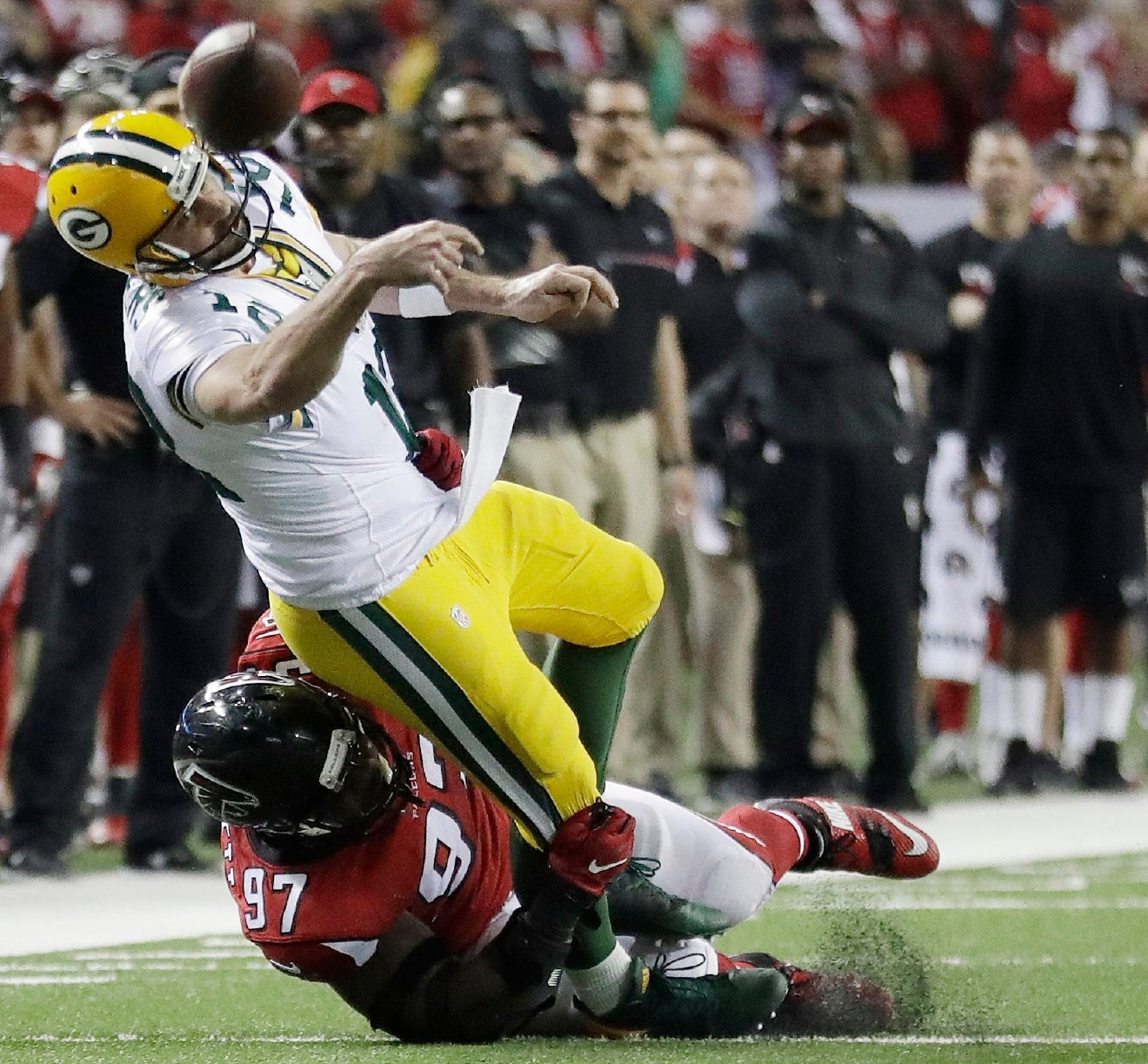 Green Bay Packers' Aaron Rodgers throws while in the grasp of Atlanta Falcons' Grady Jarrett during the second half of the NFC championship game, Sunday, Jan. 22, 2017, in Atlanta. (AP Photo/David Goldman)
