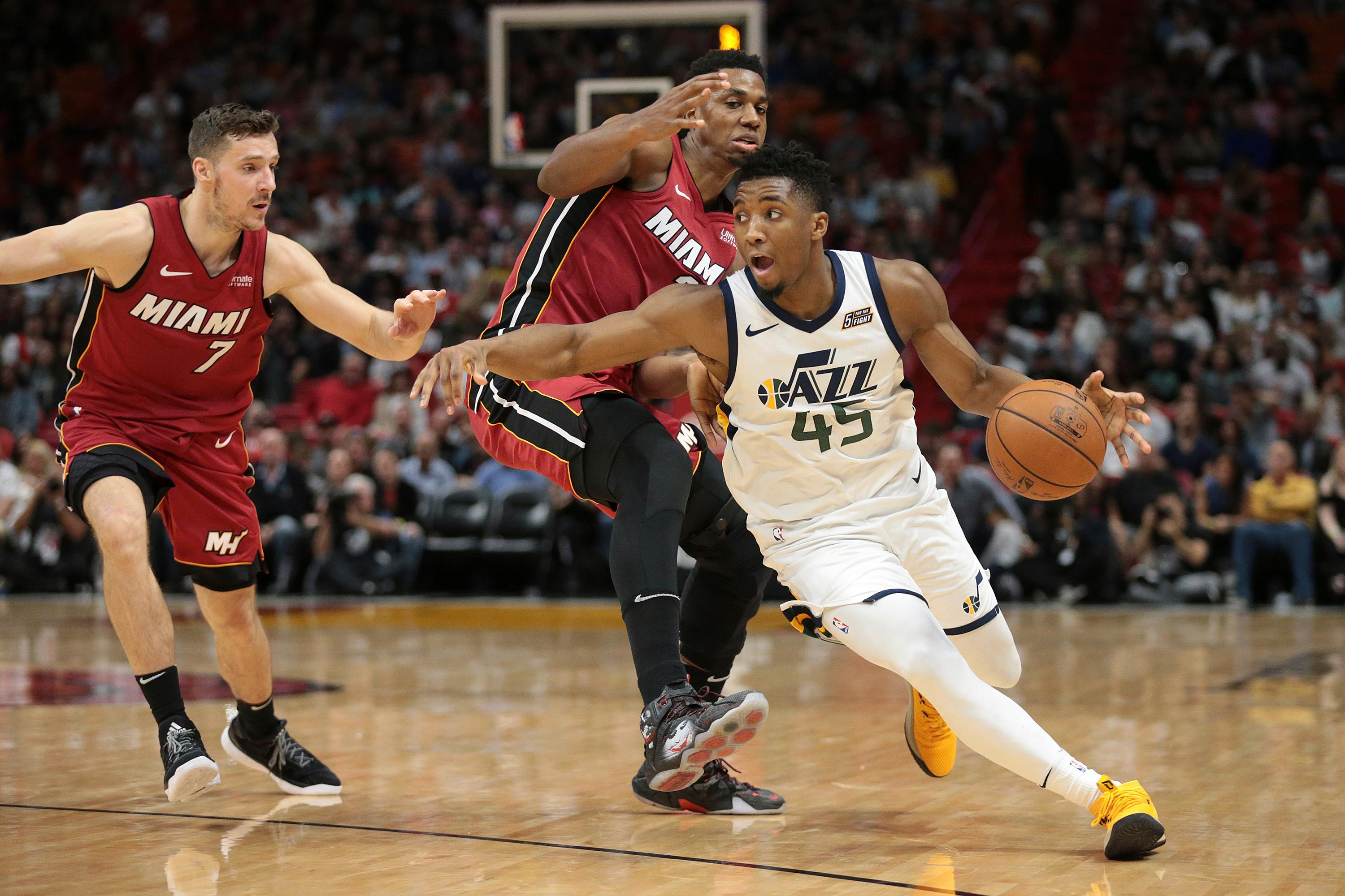 Utah Jazz guard Donovan Mitchell (45) drives to the basket past Miami Heat guard Goran Dragic (7) and center Hassan Whiteside (21) during the second half of an NBA basketball game, Sunday, Jan. 7, 2018, in Miami. (AP Photo/Joel Auerbach)