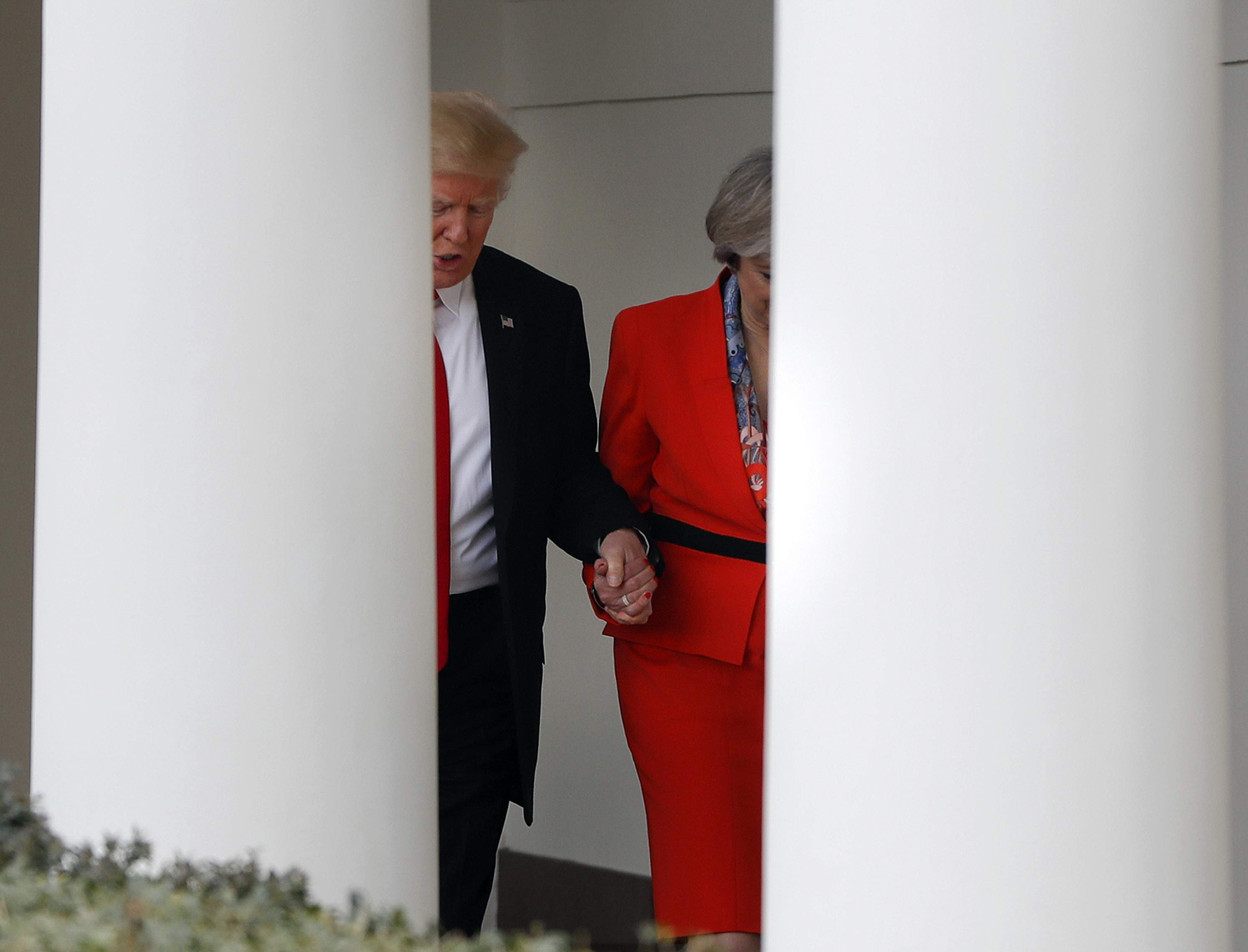 DAY 8 - In this Jan. 27, 2017, file photo, President Donald Trump holds British Prime Minister Theresa May's hand as they walk along the colonnade of the White House in Washington. (AP Photo/Pablo Martinez Monsivais, file)