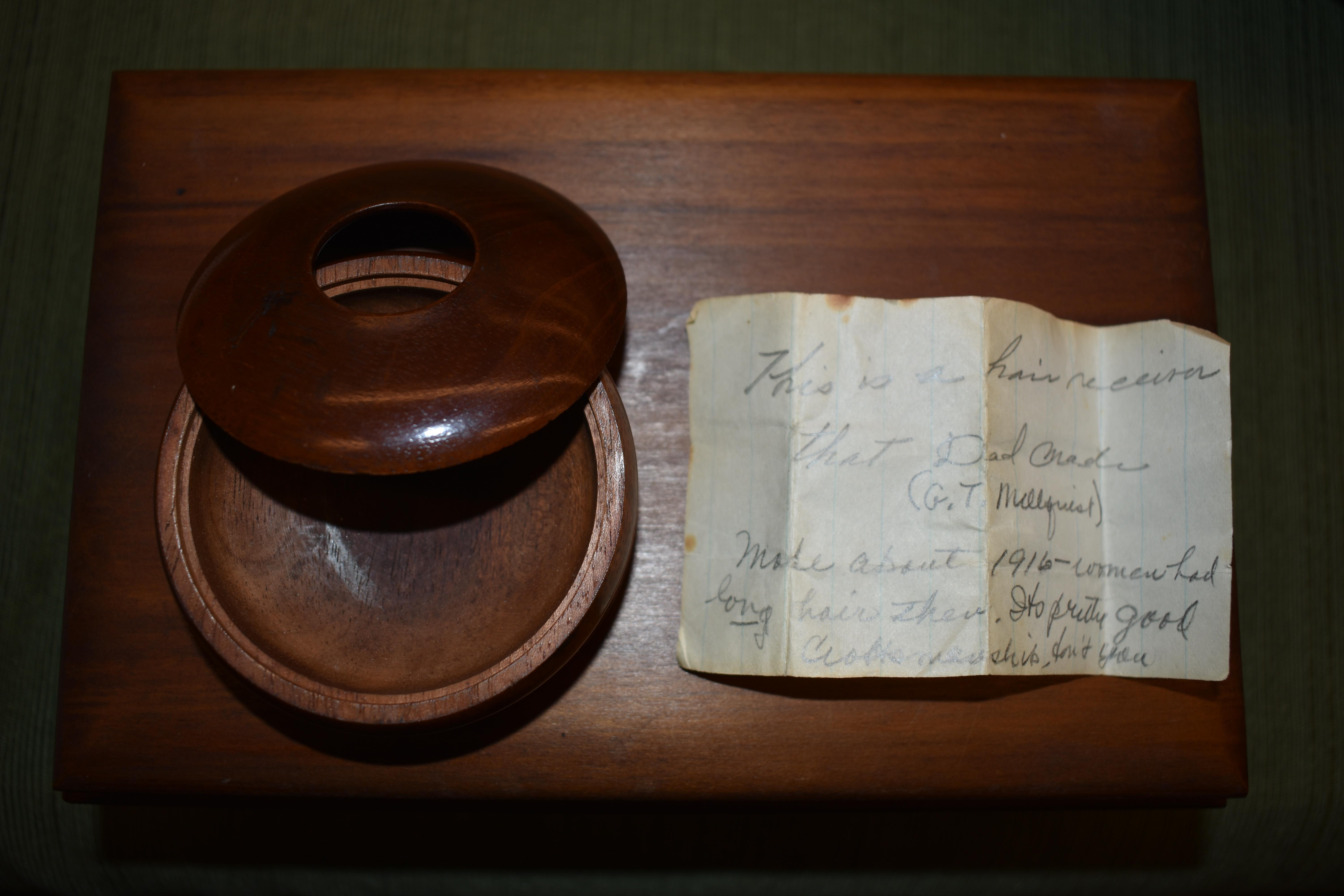 A hair receiving bowl made by Gustav Mellquist about 1916; women would save their hair and press the strands through the opening in the top piece. The note was written by Gustav's daughter, Enid who was Ray Barry's mother. Photo by Maureen Flanagan Battistella