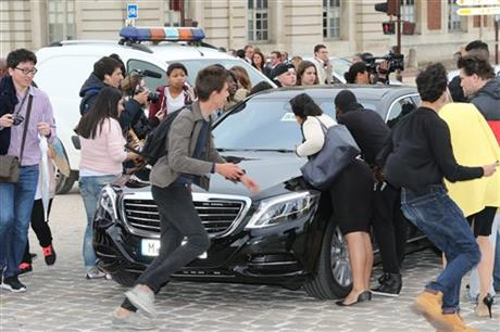 Fans gather to watch guests arriving, as they look inside one of the cars for Kim Kardashian, Kanye West and their guests, at the entrance of the Chateau de Versailles in Versailles, France, west of Paris, Friday, May 23, 2014.