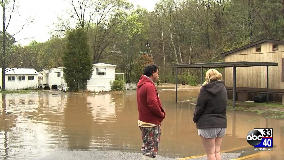 Residents observe the flash flooding at a mobile home park in Irondale, Ala., Monday, April 7, 2014.