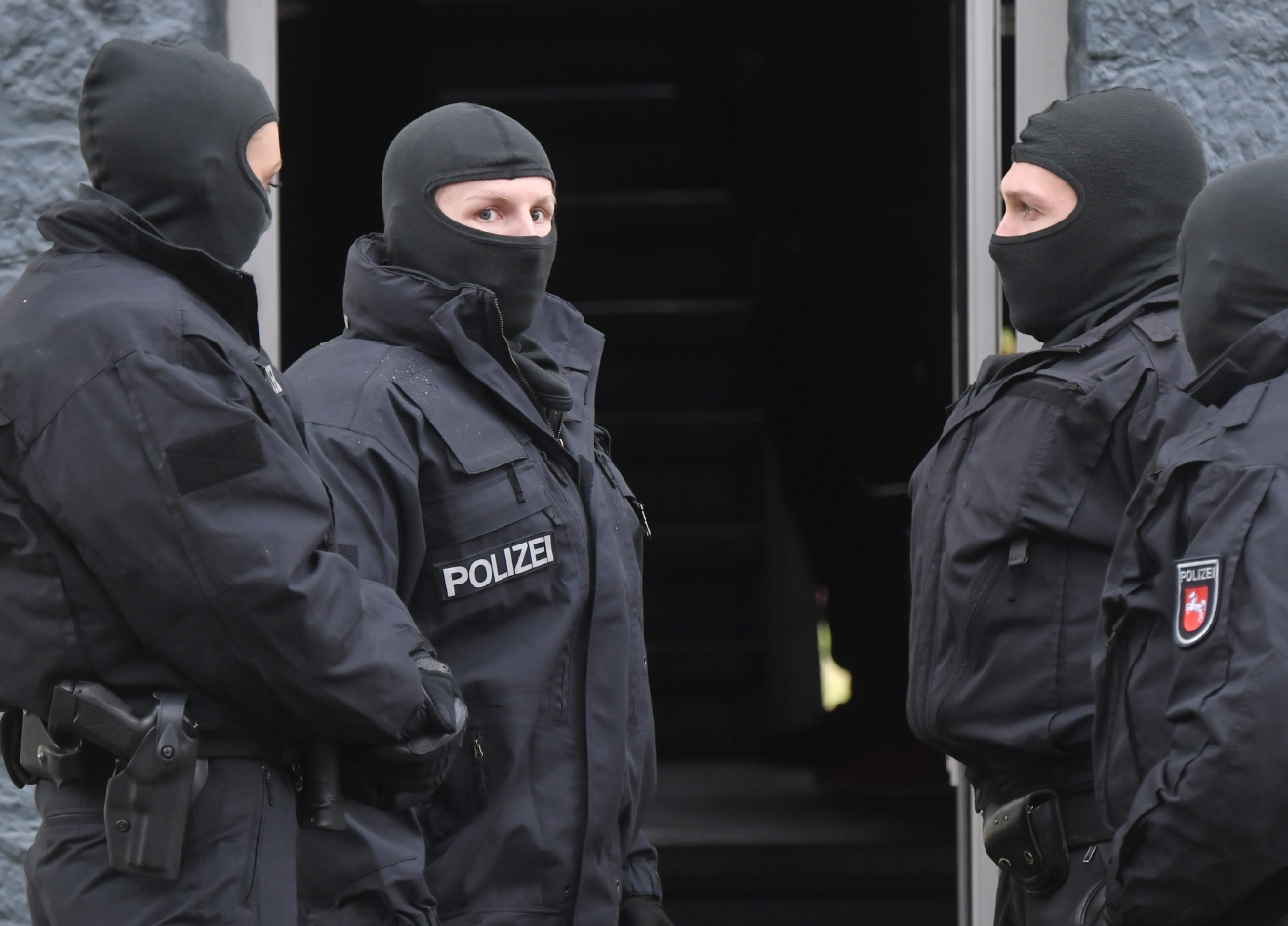 Police officers seach a residential building opposite the German-Speaking Islamic Circle Hildesheim mosque in Hildesheim, Germany, Tuesday, Nov. 8, 2016. (Julian?Stratenschulte/dpa via AP)