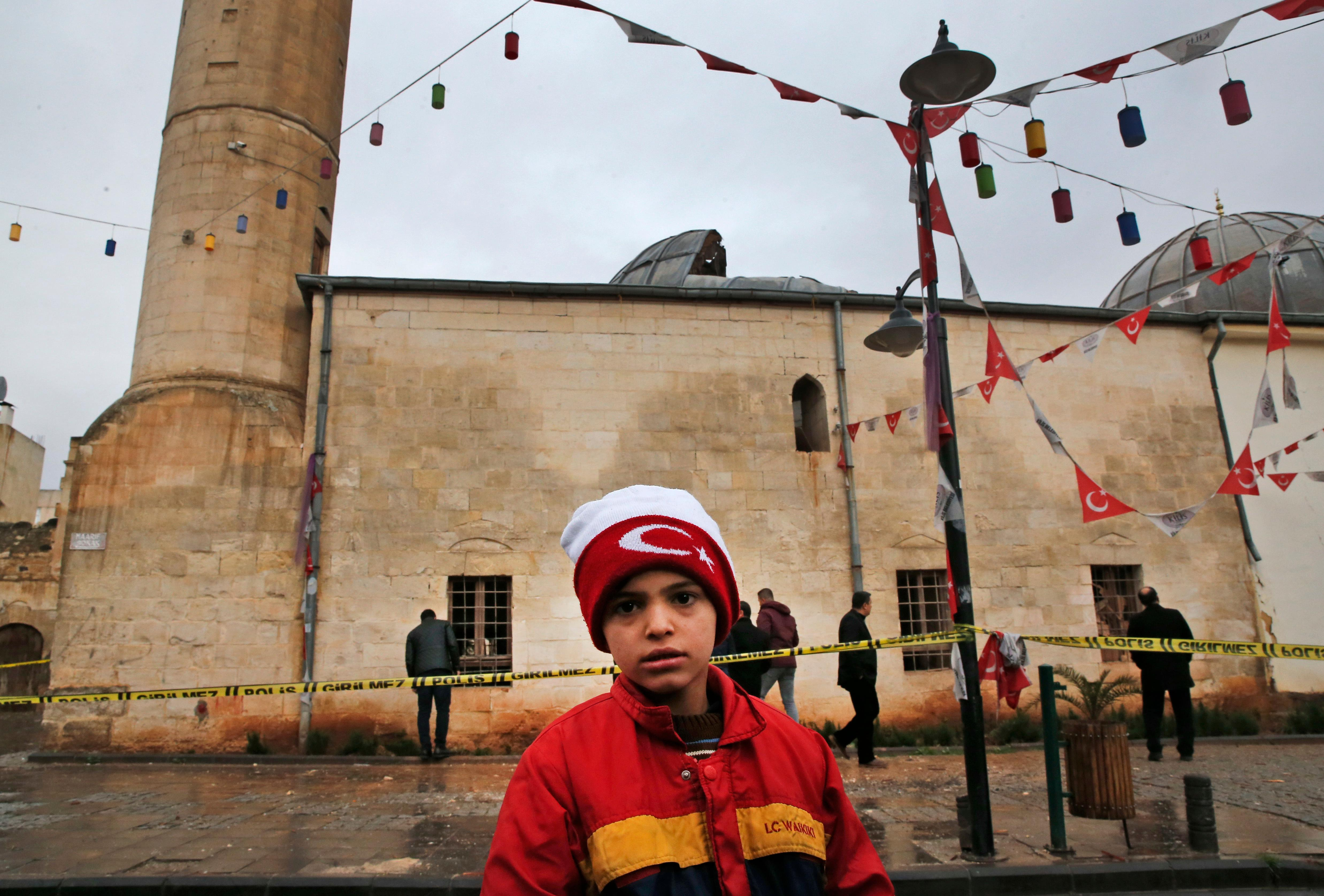 A boy stands in front of Calik mosque damaged on a rocket attack Wednesday night, in the town of Kilis, Turkey, near the border with Syria, Thursday, Jan. 25, 2018, after two rockets fired from inside Syria wounded at least 13 people when they hit a house and the mosque during evening prayers. This is the latest in a series of rocket attacks against the Turkish border town since Ankara launched a military offensive into Afrin. (AP Photo/Lefteris Pitarakis)
