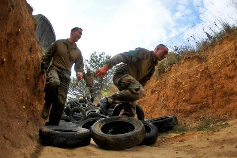 U.S. Marines and French legionnaires tackle an obstacle course after conducting a heliborne raid on Camp des Garrigues, France. The event was part of a training exercise.