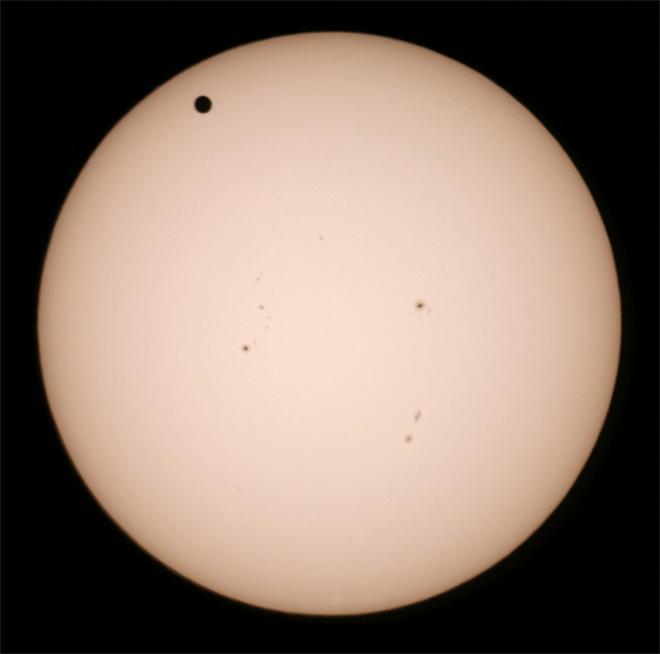 Venus, upper left, transits the sun on Tuesday, June 5, 2012, as seen from San Pedro, Calif. The black dots on the surface near the center of  the sun are sunspots. The next transit of Venus won't be for another 105 years. (AP Photo/The Daily Breeze,Chuck Bennett)  MAGS OUT; NO SALES