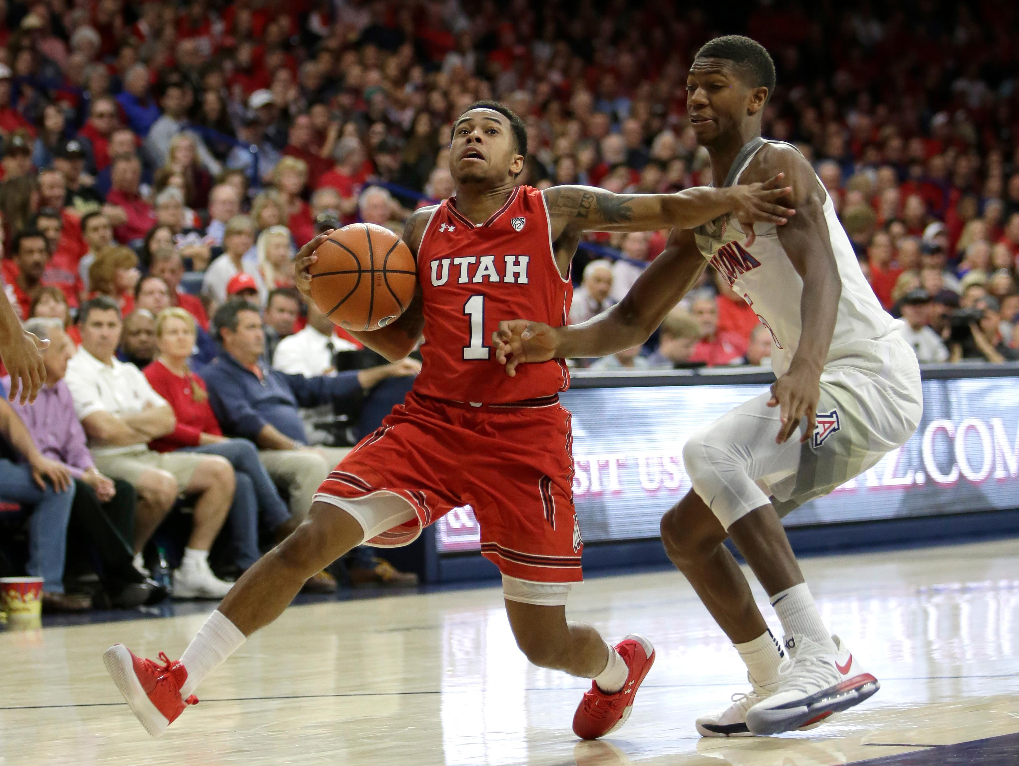 Utah guard Justin Bibbins (1) drives past Arizona forward Keanu Pinder in the first half during an NCAA college basketball game, Saturday, Jan. 27, 2018, in Tucson, Ariz. (AP Photo/Rick Scuteri)
