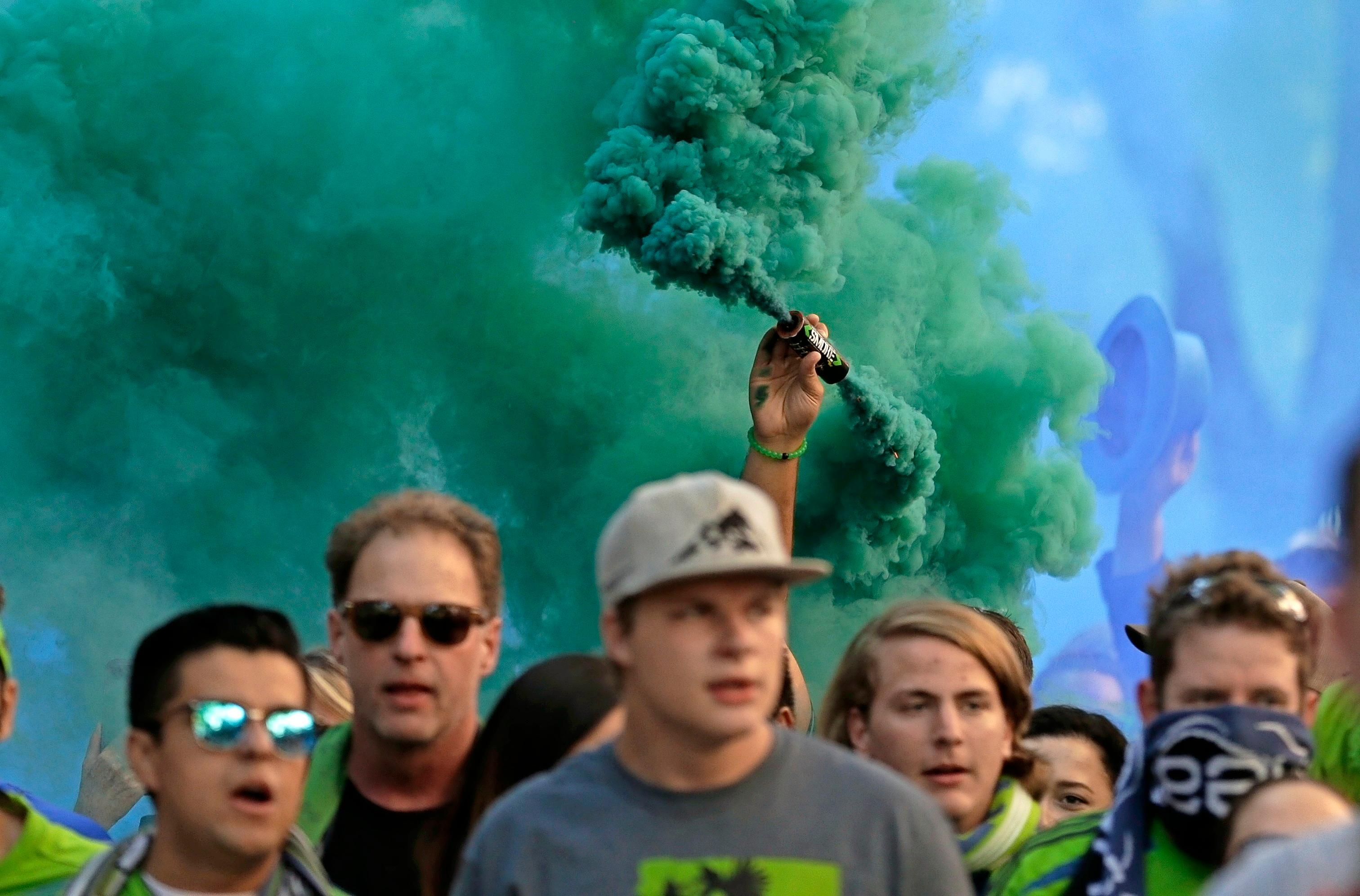 Members of the Emerald City Supporters display smoke effects as they take part in the traditional March to the Match before an MLS soccer match between the Seattle Sounders and the Portland Timbers, Sunday, Aug. 27, 2017, in Seattle. (AP Photo/Ted S. Warren)