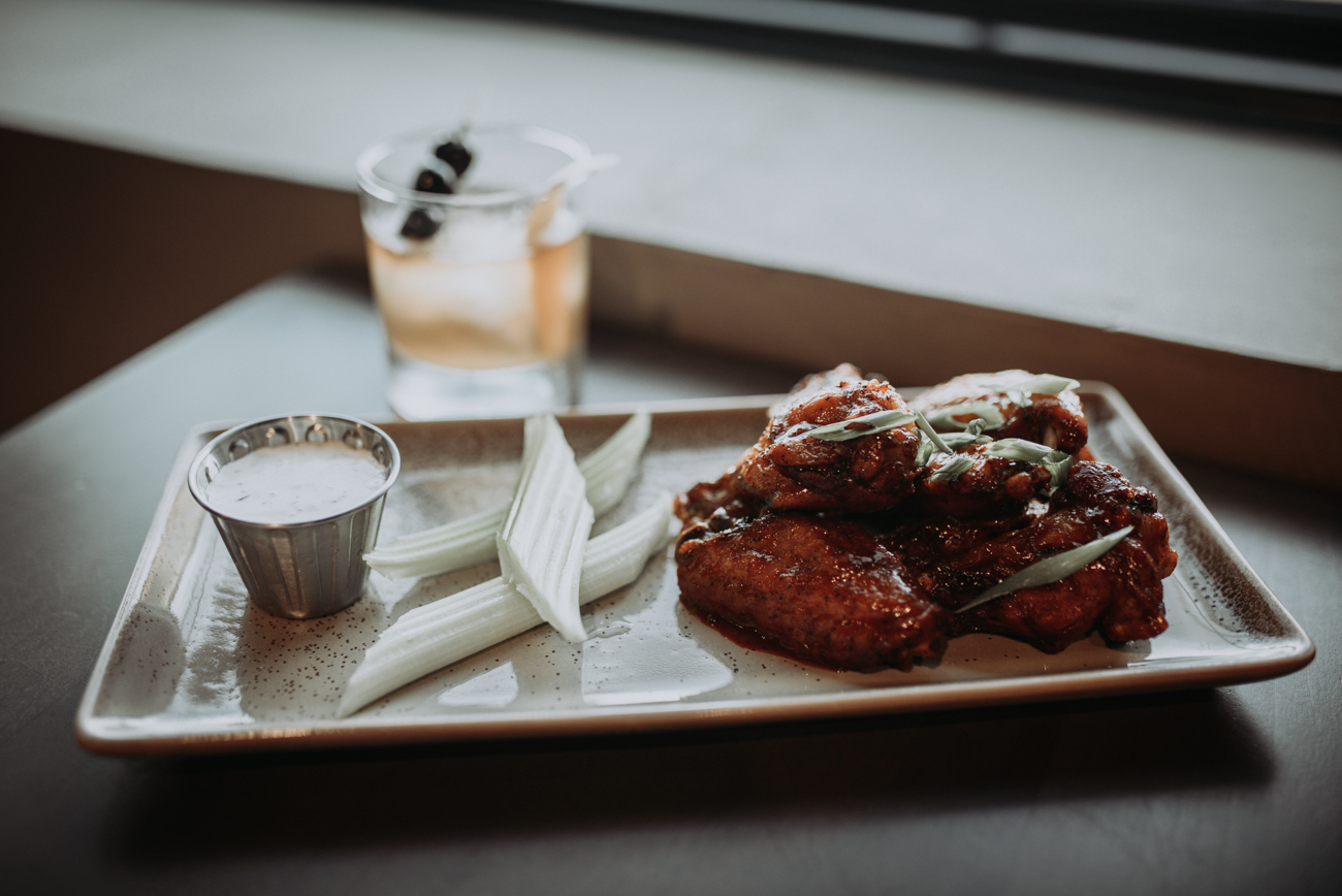 Flash fried chicken wings with honey-gochujang BBQ sauce with bleu cheese dressing alongside the Kitchen 1883 Old Fashioned / Image: Brianna Long // Published: 5.17.18