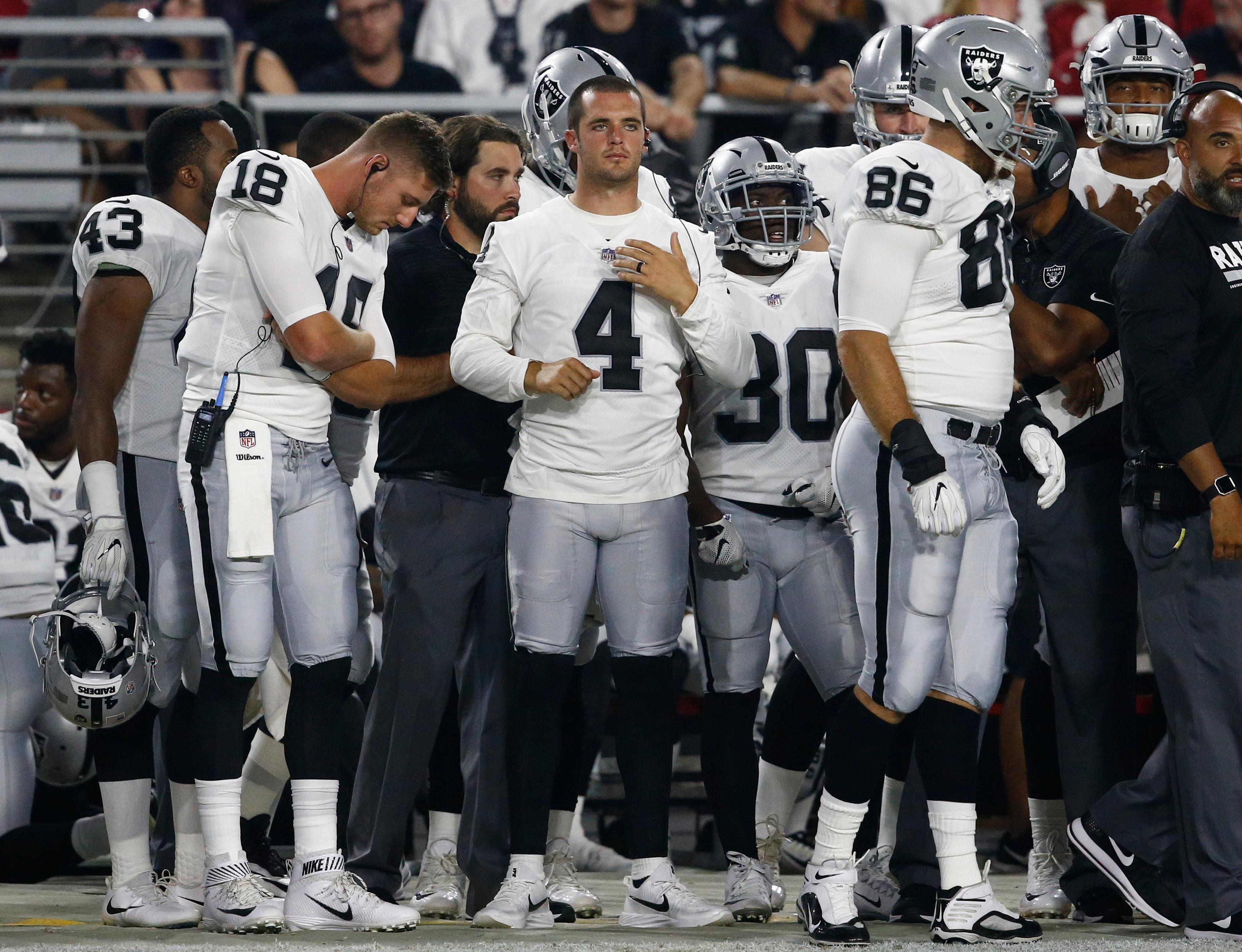 Oakland Raiders quarterback Derek Carr (4) watches from the sidelines during the first half of the team's NFL preseason football game against the Arizona Cardinals, Saturday, Aug. 12, 2017, in Glendale, Ariz. (AP Photo/Ross D. Franklin)