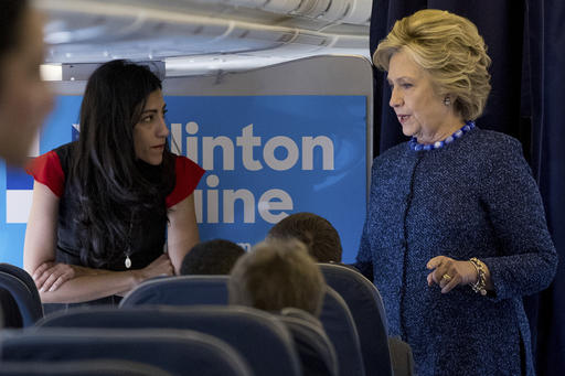 FILE - In this Oct. 28, 2016 file photo, Democratic presidential candidate Hillary Clinton speaks with senior aide Huma Abedin aboard her campaign plane at Westchester County Airport in White Plains. The longtime Hillary Clinton aide at the center of a renewed FBI email investigation testified under oath four months ago she never deleted old emails, despite promising in 2013 not to take sensitive files when she left the State Department.  (AP Photo/Andrew Harnik, File)