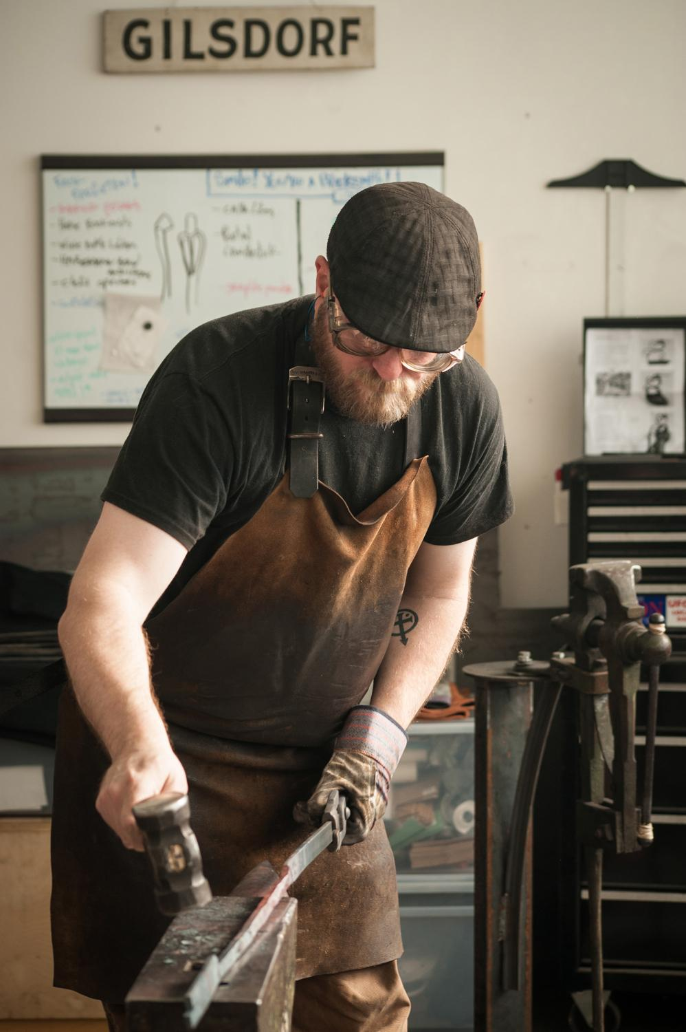 Mark Gilsdorf works on a piece of steel in his studio in the Essex Art Studios. Gilsdorf began learning the craft in 2007 and became a full-time blacksmith in 2013. / Image: Melissa Doss Sliney