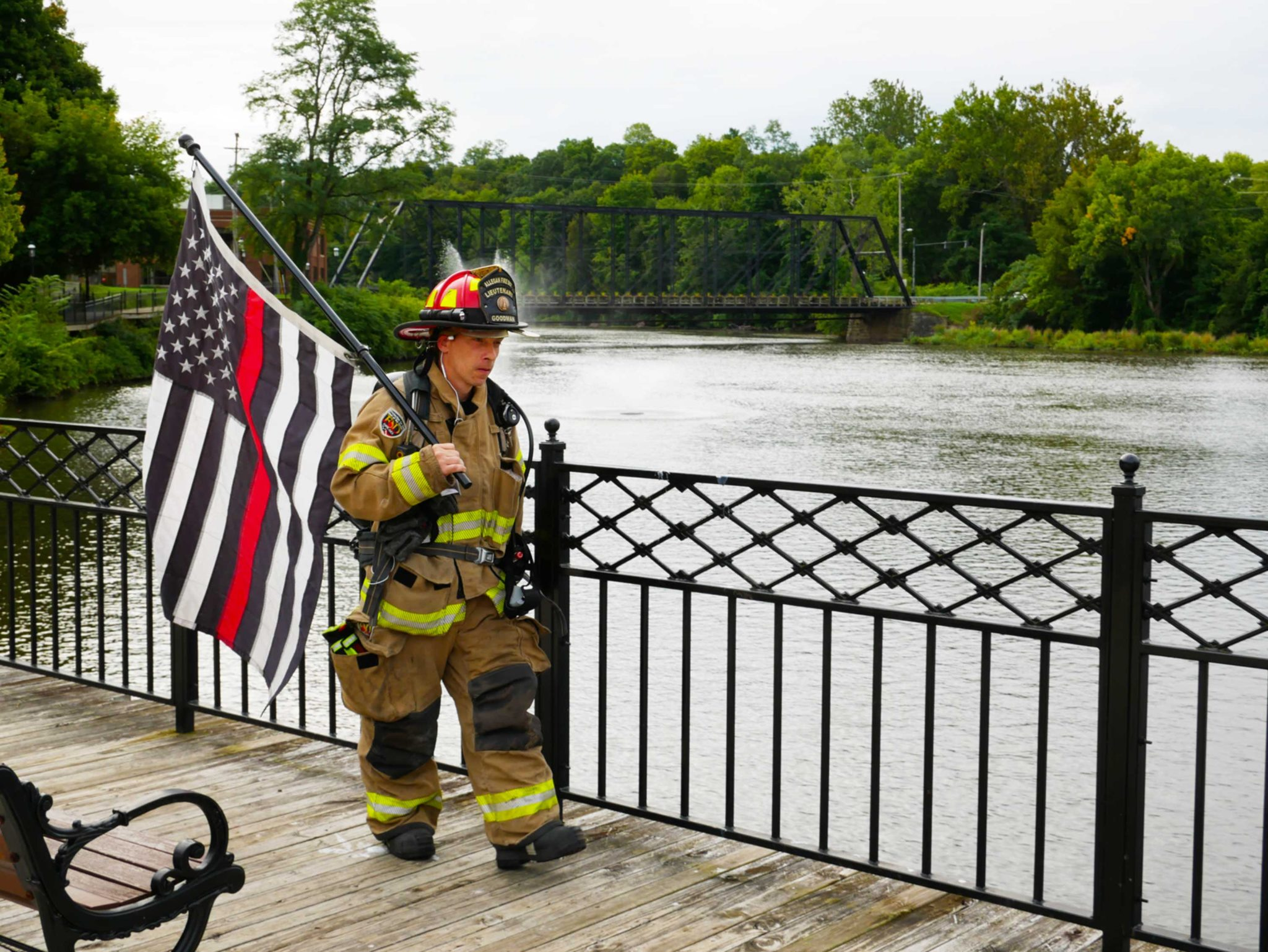 Allegan Fire Department Lieutenant Chris Goodman walking the streets on September 11, 2020. With full turnout gear and an american flag with a red stripe, he walked downtown Allegan, in remembrance of those that died on September 11, 2001. (WWMT/Felicia Belden)