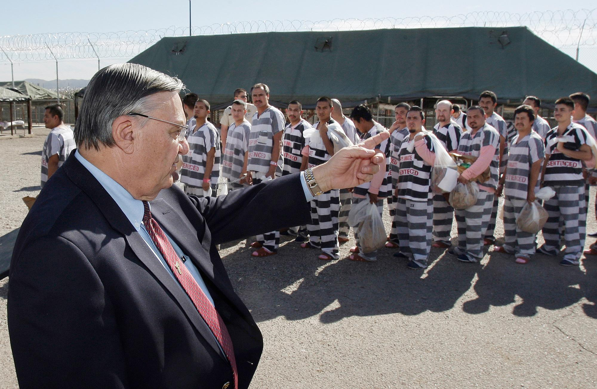 FILE- In this Feb. 4, 2009 file photo, Maricopa County Sheriff Joe Arpaio, left, orders approximately 200 convicted illegal immigrants handcuffed together in Tent City in Phoenix for incarceration until their sentences are served and they are deported to their home countries. Arpaio has been convicted of a criminal charge Monday, July 31, 2017, for disobeying a court order to stop traffic patrols that targeted immigrants in a conviction that marks a final rebuke for the former sheriff and politician who once drew strong popularity from such crackdowns but was booted from office amid voter frustrations over his deepening legal troubles.(AP Photo/Ross D. Franklin, File)