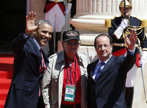 "U.S. President Barack Obama, left, and French President Francois Hollande, right, waves with World War II veteran Kenneth ""Rock"" Merritt."