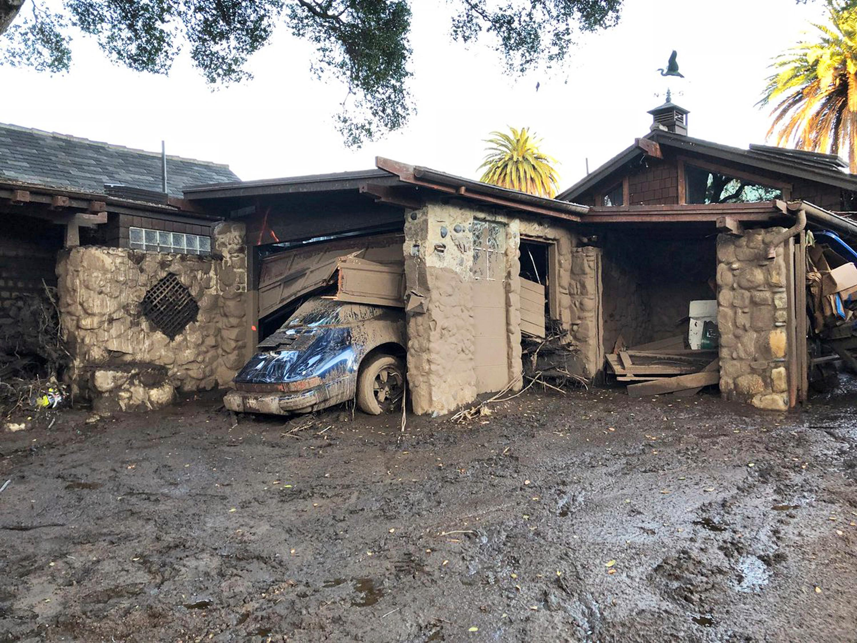 This photo provided by the Santa Barbara County Fire Department shows damage from mud, boulders, and debris that destroyed homes that lined Montecito Creek near East Valley Road in Montecito, Calif., Wednesday, Jan. 10, 2018. Anxious family members awaited word on loved ones Wednesday as rescue crews searched grimy debris and ruins for more than a dozen people missing after mudslides in Southern California Tuesday destroyed over a 100 houses, swept cars to the beach and left more than a dozen victims dead.  (Mike Eliason/Santa Barbara County Fire Department via AP)