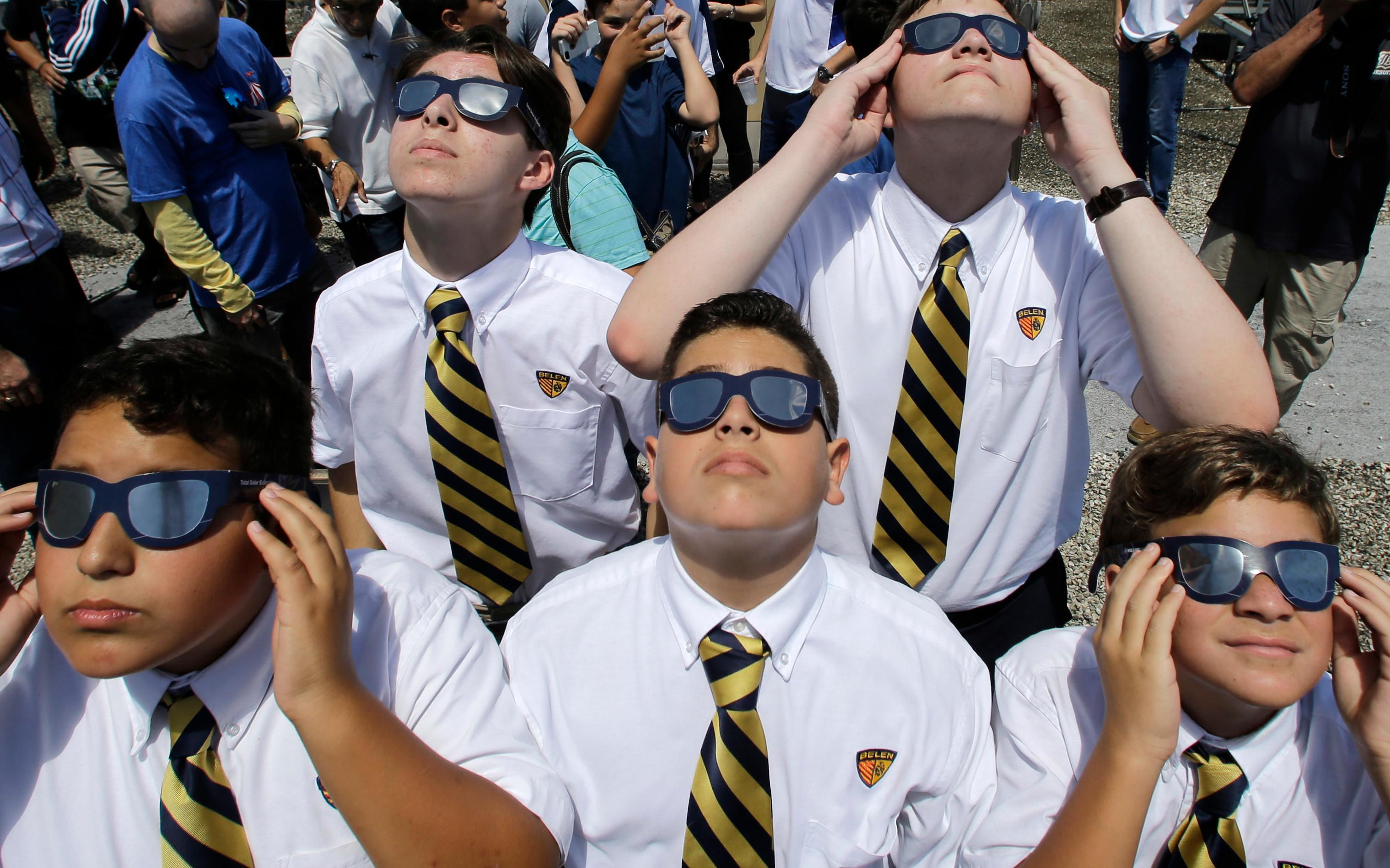 Belen Jesuit Preparatory School students look through solar glasses as they watch the eclipse, Monday, Aug. 21, 2017, in Miami. (AP Photo/Alan Diaz)