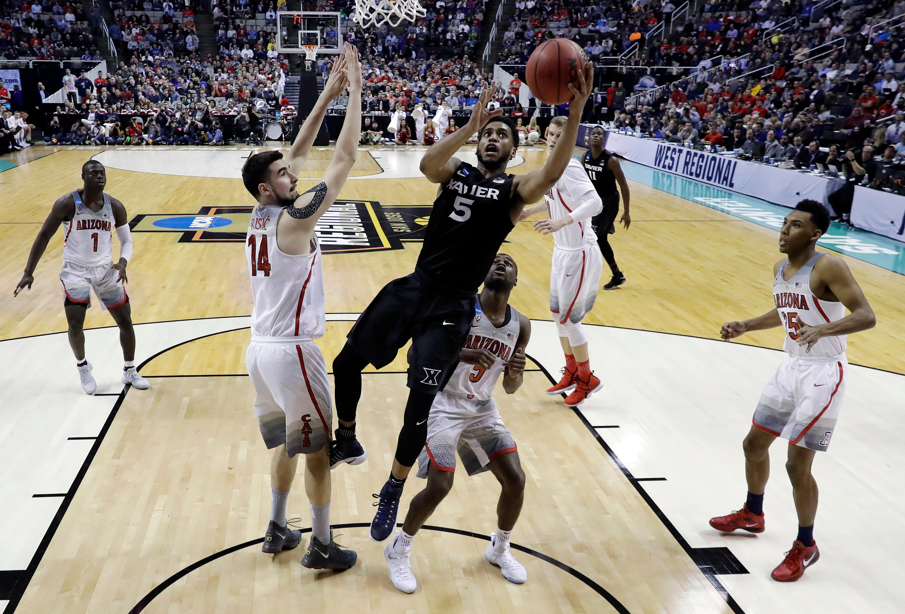 FILE - In this March 23, 2017, file photo, Xavier guard Trevon Bluiett (5) drives to the basket against Arizona during the second half of an NCAA men's college basketball tournament regional semifinal in San Jose, Calif. Big East coaches have given Bluiett first-team all-conference honors each of the last two seasons. Bluiett ranked second in the Big East in scoring (18.5) and 10th in rebounding (5.7) last season while also making 2.5 3-pointers per game. (AP Photo/Tony Avelar, File)