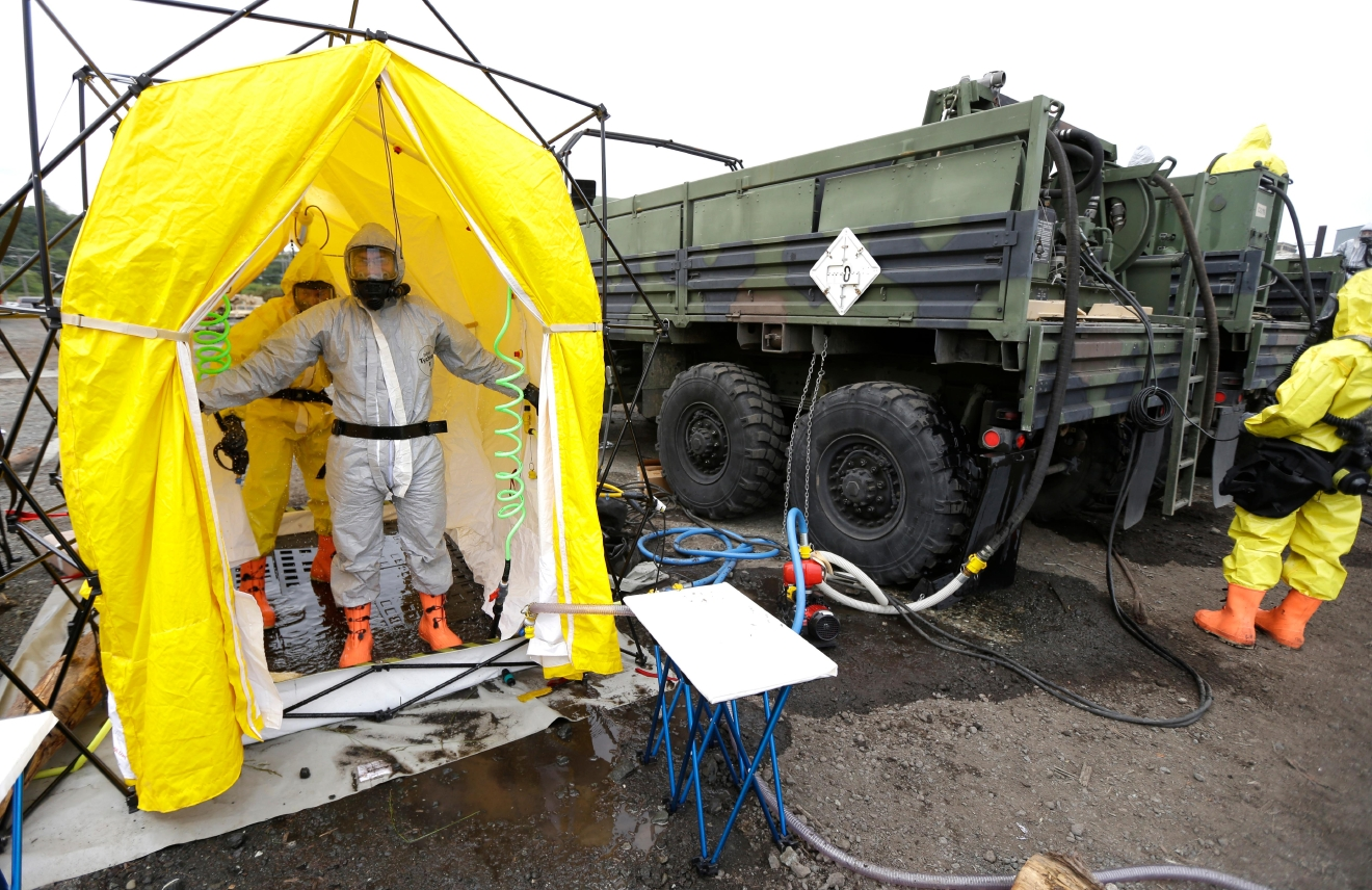 Members of the Washington Army National Guard 792nd Chemical Company from Grandview, Wash., demonstrate a decontamination station for people and vehicles, Wednesday, June 8, 2016, in Port Angeles, Wash. The exercise was part of a massive earthquake and tsunami drill called Cascadia Rising, that is built around the premise of a 9.0 magnitude earthquake 95 miles off of the coast of Oregon that results in a tsunami. In the event of an actual tsunami, the soldiers will decontaminate people who come in contact with polluted or hazardous substances stirred up by a tsunami. (AP Photo/Ted S. Warren)
