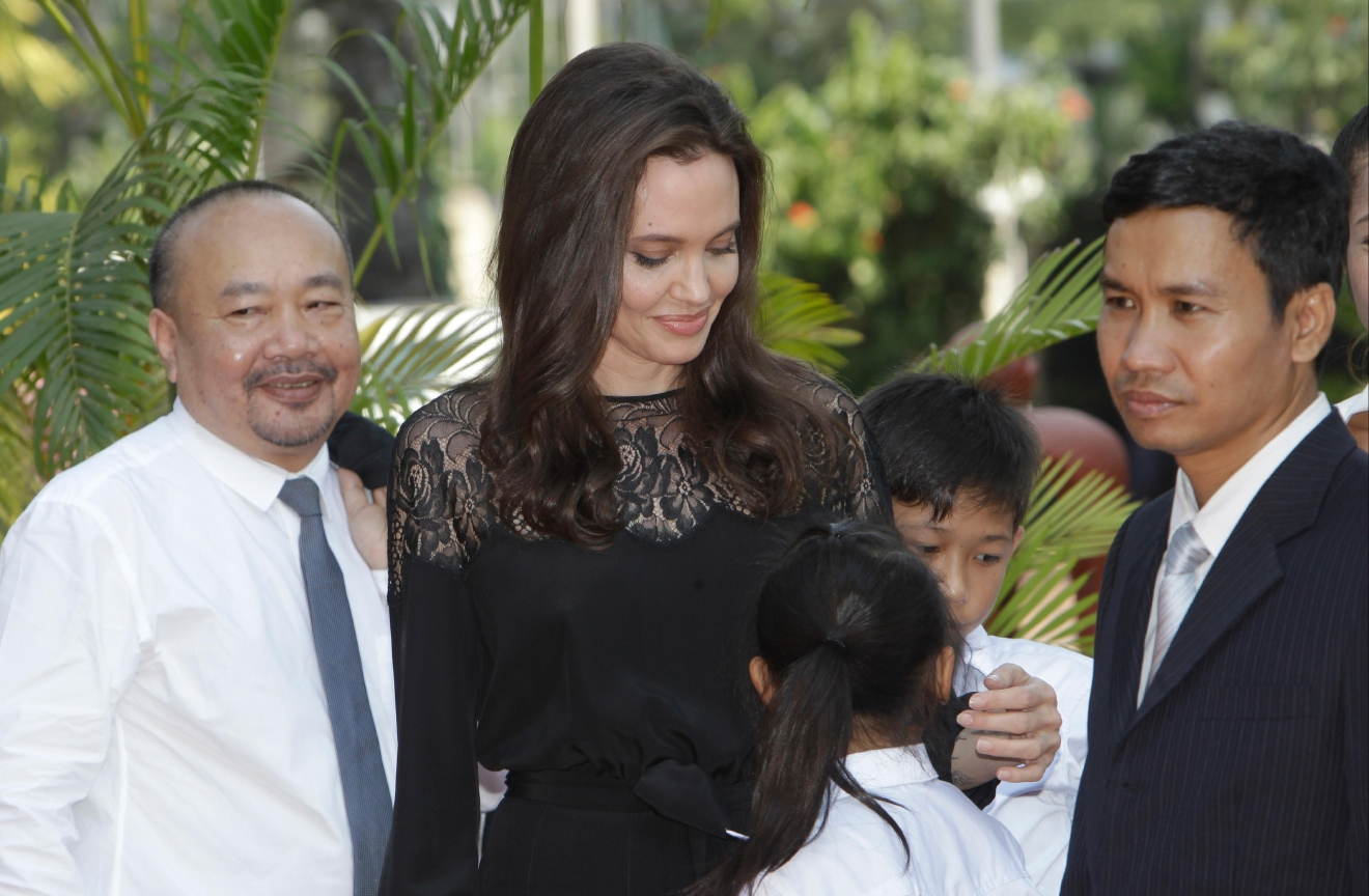 "Hollywood actress Angelina Jolie, center, stands together with Cambodian film maker Rithy Panh, left, as they wait for the start a press conference in Siem Reap province, Cambodia, Saturday, Feb. 18, 2017. Jolie on Saturday launches her two-day film screening of ""First They Killed My Father"" is presiding over by King Sihamoni, in Angkor complex in Siem Reap province. (AP Photo/Heng Sinith)"
