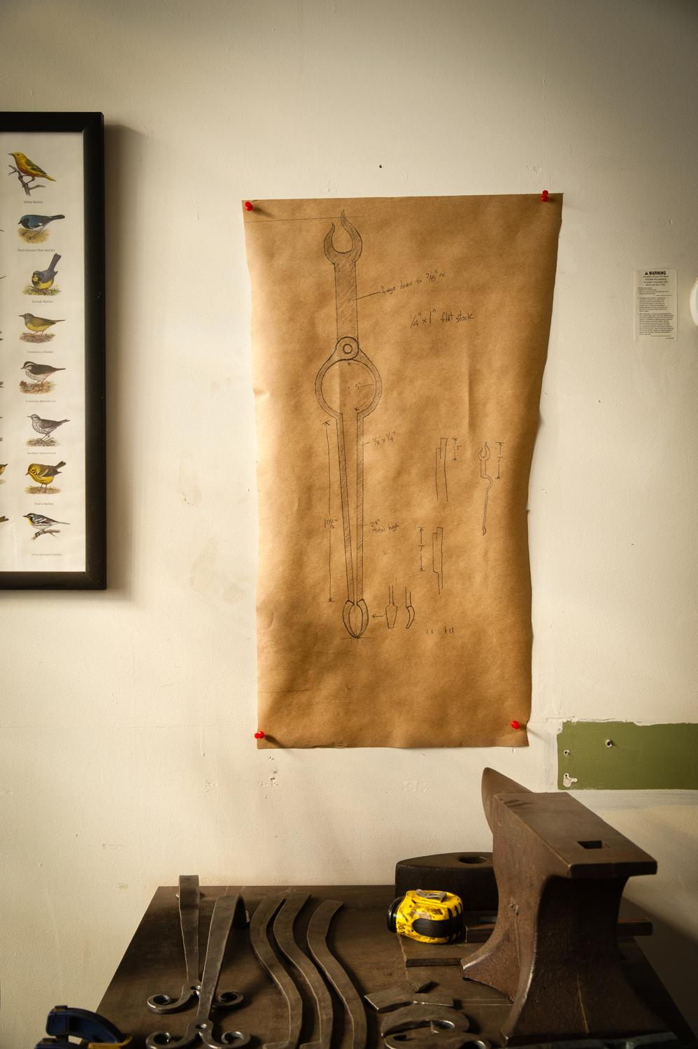 A sketch of Gilsdorf's current project, a commission for fireplace tongs, hangs on the wall. / Image: Melissa Doss Sliney