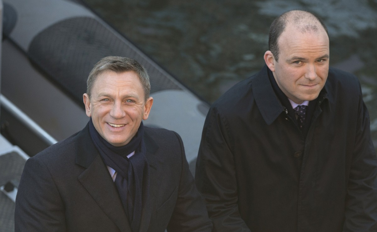 "FILE - In this Tuesday, Dec. 16, 2014 file photo, actors Daniel Craig, left, and Rory Kinnear smile for photographers as they film a scene for the new James Bond film, Spectre, in London. 007 star Daniel Craig and the film's other luminaries will be at the October world premiere of the new James Bond film ""Spectre"", and Palace officials said Wednesday Sept. 16, 2015, they will be joined on the red carpet by Prince William and his wife Kate and Prince Harry. (AP Photo/Alastair Grant, File)"