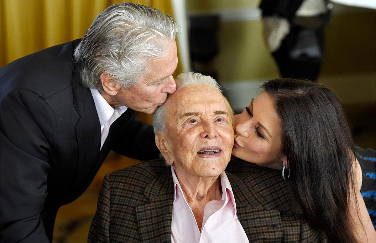 Actor Kirk Douglas, center, gets a kiss from his son Michael Douglas, left, and Michael's wife Catherine Zeta-Jones during his 100th birthday party at the Beverly Hills Hotel on Friday, Dec. 9. 2016, in Beverly Hills, Calif. (Photo by Chris Pizzello/Invision/AP)