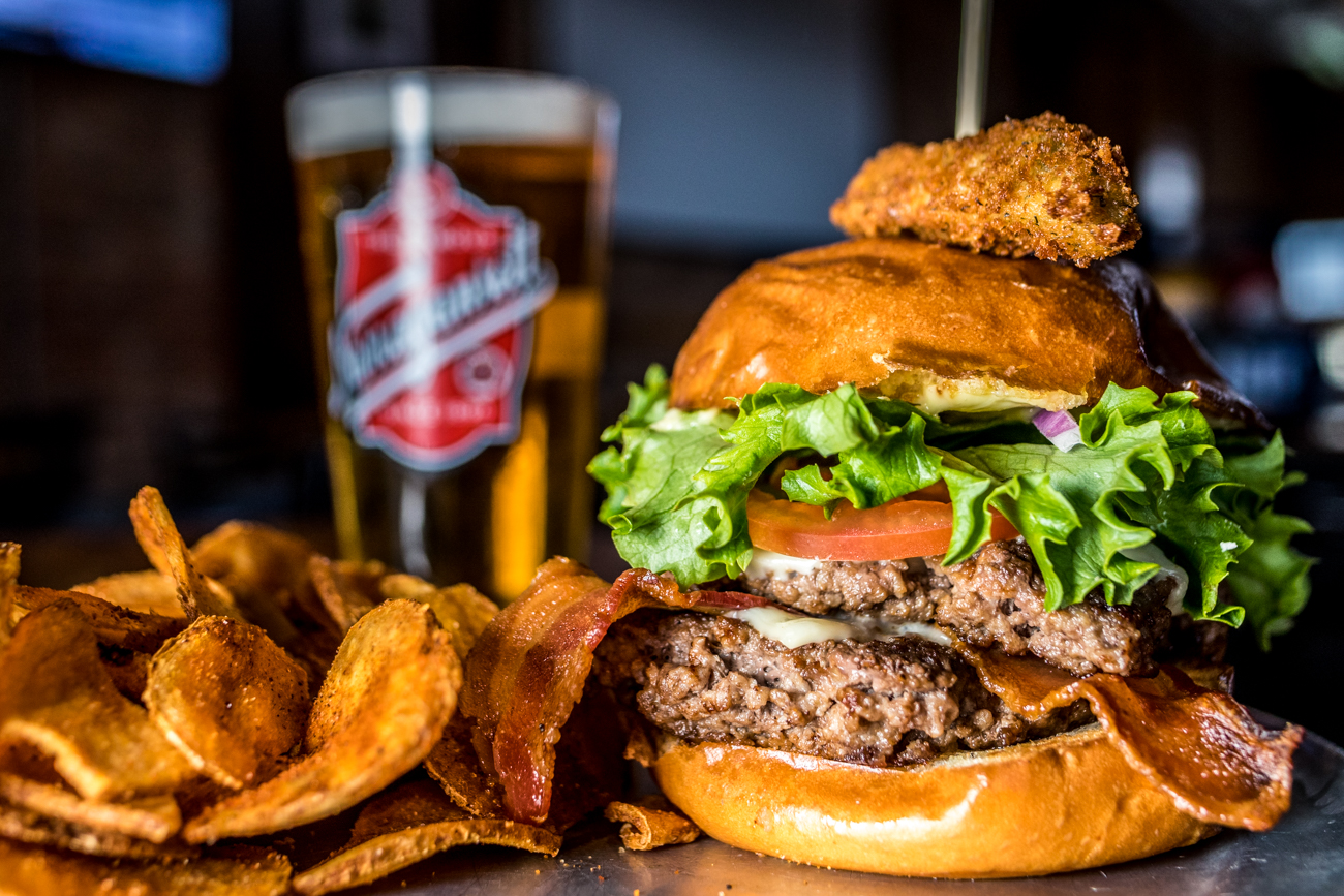 East End Burger: American cheese, bacon, red onion, shredded lettuce, and tomato & garlic aioli served on challah with a fried pickle topper and paired with a Narragansett Lager / Image: Catherine Viox // Published: 3.12.20