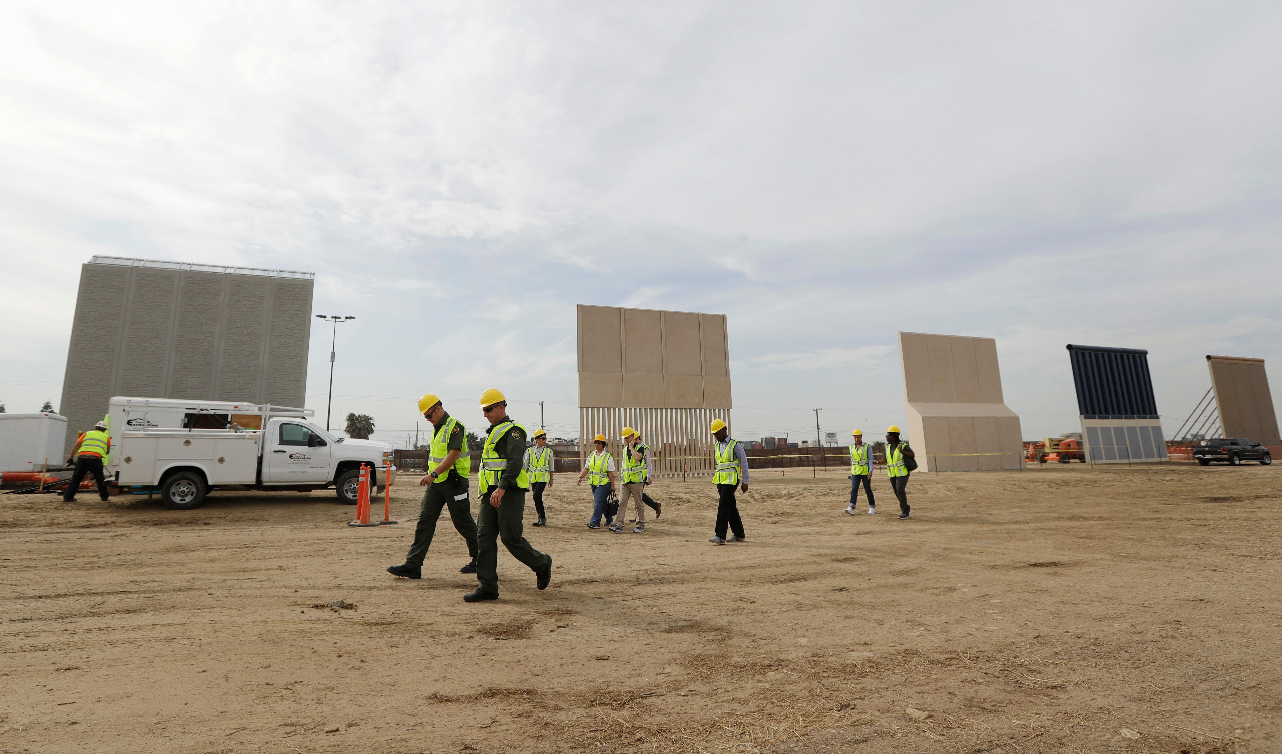In this Oct. 19, 2017 file photo, people pass border wall prototypes as they stand near the border with Tijuana, Mexico, in San Diego.  A U.S. official says recent testing of prototypes of President Donald Trump's proposed wall with Mexico found their heights should stop border crossers. (AP Photo/Gregory Bull, File)