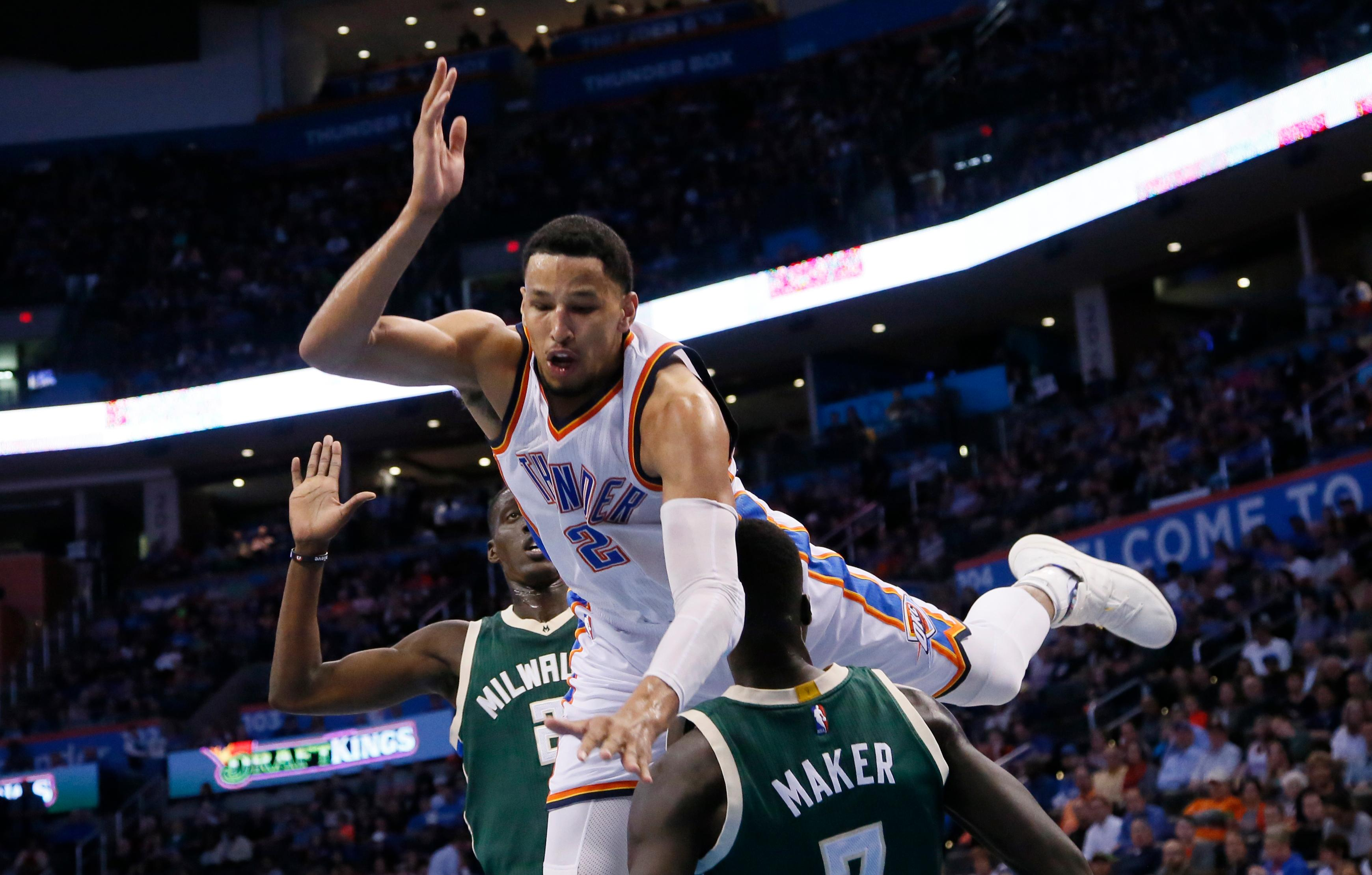 Oklahoma City Thunder forward Andre Roberson, center, falls over Milwaukee Bucks forward Thon Maker, right, and is called for an offensive foul in the third quarter of an NBA basketball game in Oklahoma City, Tuesday, April 4, 2017. Oklahoma City won 110-79. Bucks Tony Snell is at left. (AP Photo/Sue Ogrocki)