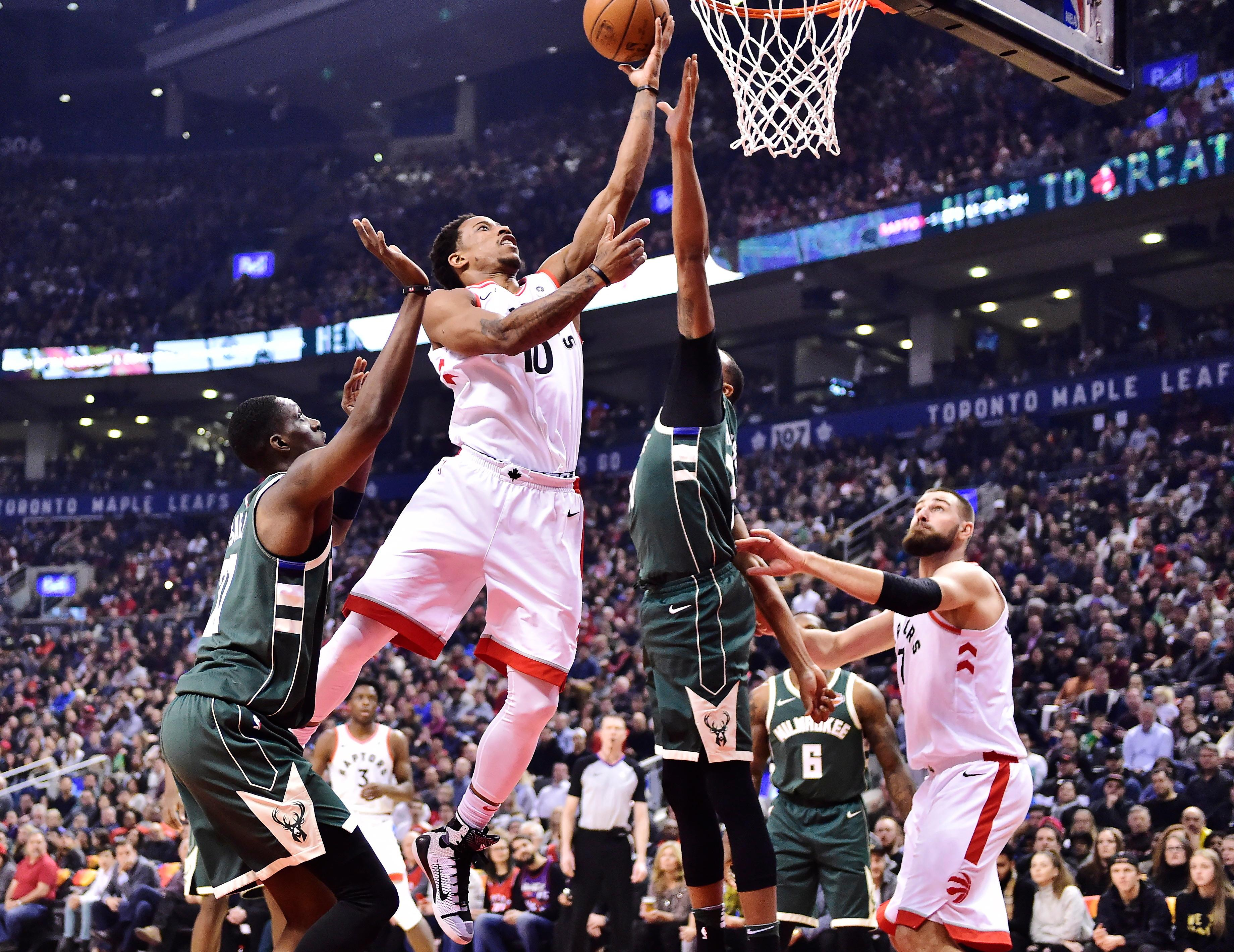 Toronto Raptors guard DeMar DeRozan (10) shoots over Milwaukee Bucks forward John Henson (31) as Bucks guard Tony Snell, left, looks on during first half action in Toronto on Monday, Jan. 1, 2018. (Frank Gunn/The Canadian Press via AP)