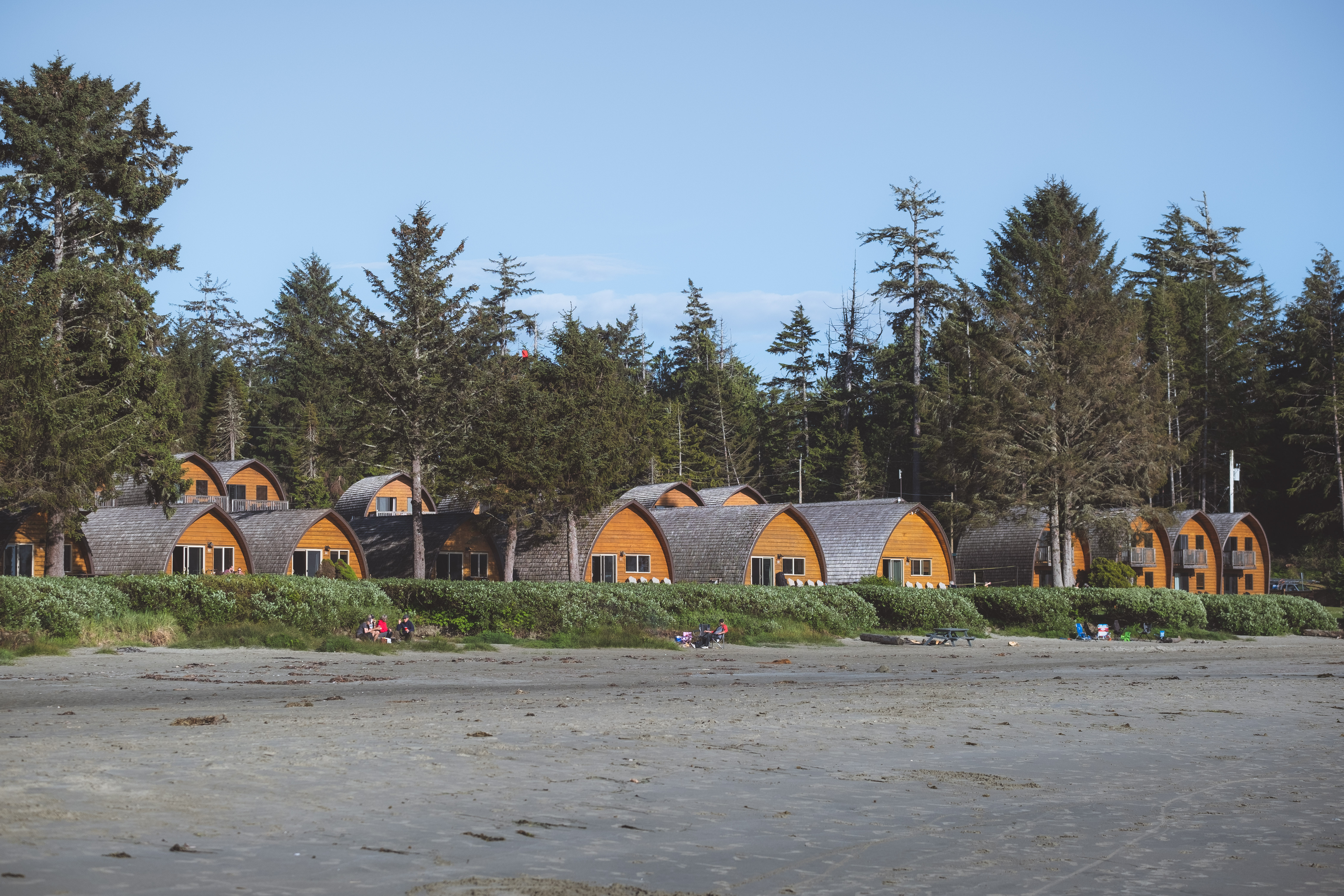 "Sporting a variety of charming ""beehive"" cedar cabins originally built in 1976, Ocean Village Resort offers patrons an affordable option to experience Tofino's gorgeous coastlines. Located right on Mackenzie Beach, enjoy panoramic views of the ocean while you soak up a sunset by a beach fire, or get out on the water for a paddle board or surf. Including amenities such as a heated pool and hot tub, an outdoor BBQ area, on-site surf shack, and access to a variety of fun and games for beach play, there is something to do for the whole family. Also, with a commitment to reducing their environmental footprint through on demand hot water systems and an extensive recycling and composting program, you can feel good about supporting a sustainable community. (Image: Ryan McBoyle / Seattle Refined){ }"