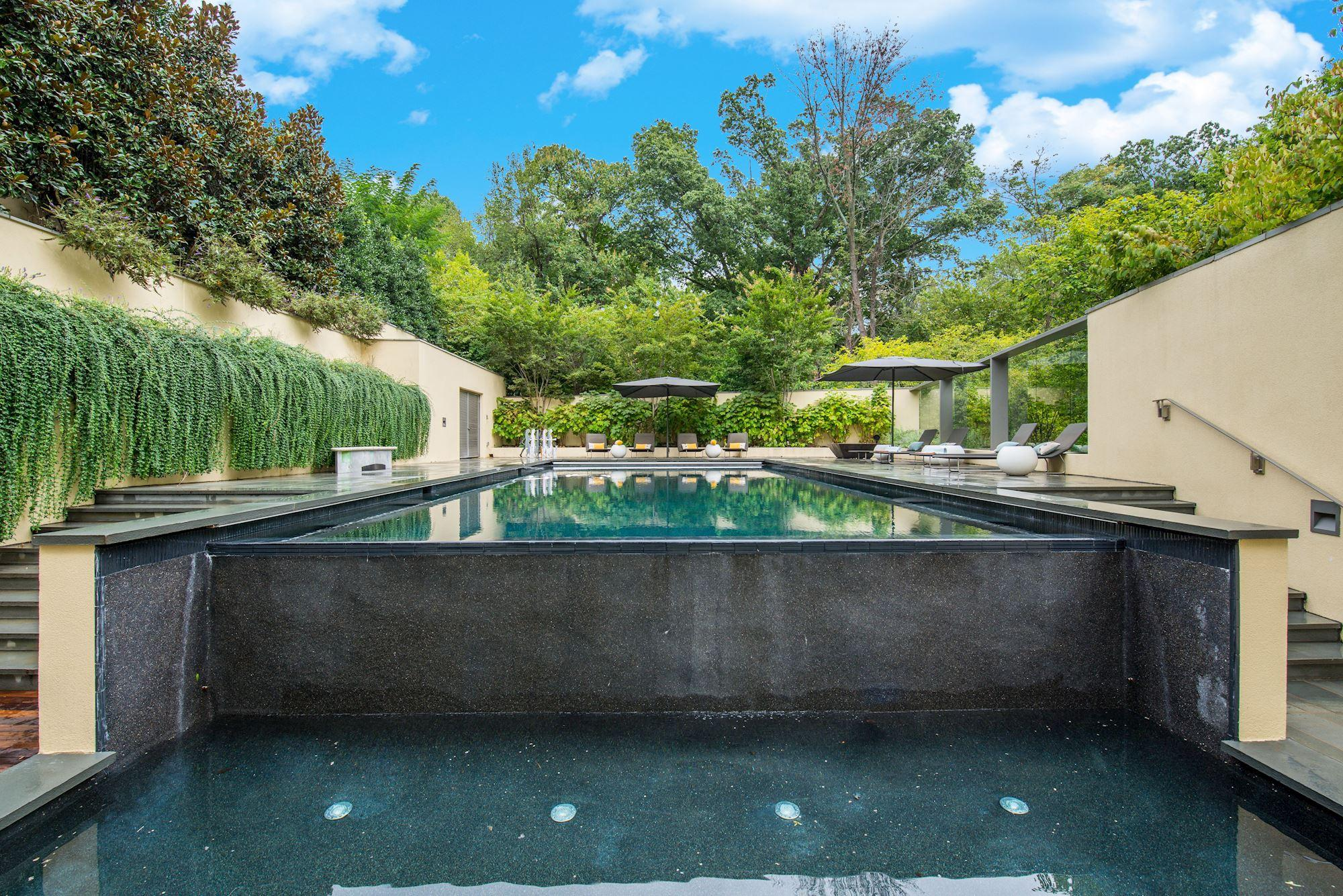 This gorgeous home listed by Washington Fine Properties is a true hidden gem overlooking Rock Creek Park. Built in 2010, it sits on a nearly 18,000-square-foot lot and is currently listed for $11.5 million, down $2 million from the original $13.5 million listing price. Natural light abounds in this modern marvel, particularly thanks to the floor to ceiling windows in the two-story great room with 180 degree park views. Everything about the home screams luxury from the eight-car garage to the custom ebonized white oak cabinetry and Gaggenau ovens in the kitchen, the 21-seat media room with a star light pattern fiber optic ceiling, the owner's suite with dual water closets, spa shower, soaking tub and make-up and hair salon. Enjoy the gallery and visit  wfp.com for more info on the lot. (Image: HomeVisit)