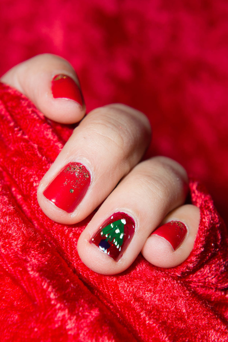 "What better way to get into the holiday mood than a little ""treat yo-self"" manicure? 2017 was a long year, so you definitely earned a little pampering. We were looking to put a little pizazz into our holiday look without going too over the top, so we headed over to Night Light Nails in Wallingford to see what they might be able to whip up.After chatting it over a little, we opted for a Christmas tree accent nail on the ring finger and a pretty, gold flecked ombre red on the other eight digits. A couple swipes of OPI's Ruby Pumps later, we had a wonderfully festive mani you could practically rock year round. Click on for the holiday inspired look. (Image: Chona Kasinger / Seattle Refined)"