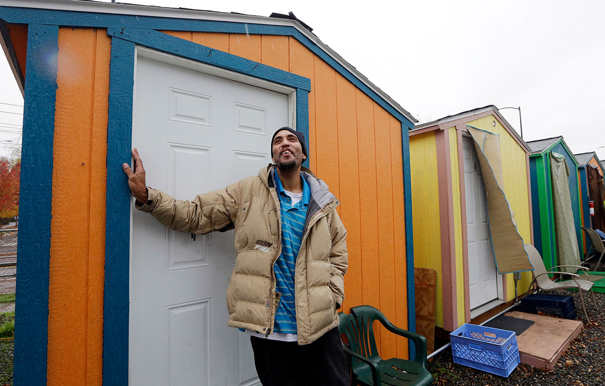 FILE - In this Thursday, Nov. 9, 2017, file photo, Tyson King stands at the door of his tiny house at a homeless encampment in Seattle. In the absence of legislation to incentivize the acceptance of Section 8 vouchers, politicians and advocates have been scrambling to keep up with the surge of unsheltered residents in the state. One answer in Seattle has been the so-called tiny houses, portable 120-square-foot shacks of simple wood construction, which now include seven villages with a capacity to house 350 people since its start in 2015. (AP Photo/Elaine Thompson, File)